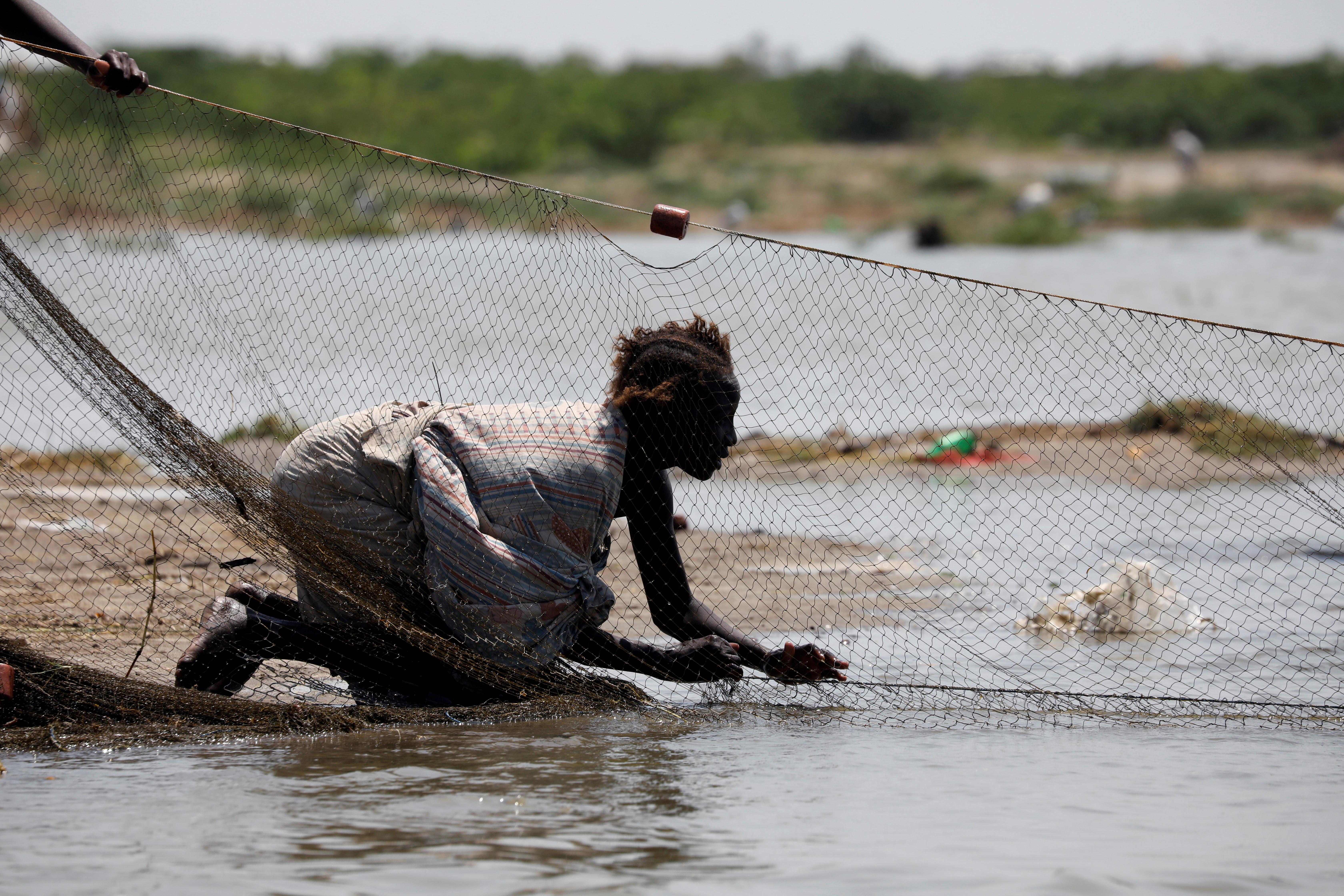 a woman pulls in a fishing net on a beach at Lake Turkana, near the town of Kalokol, Turkana county, Kenya