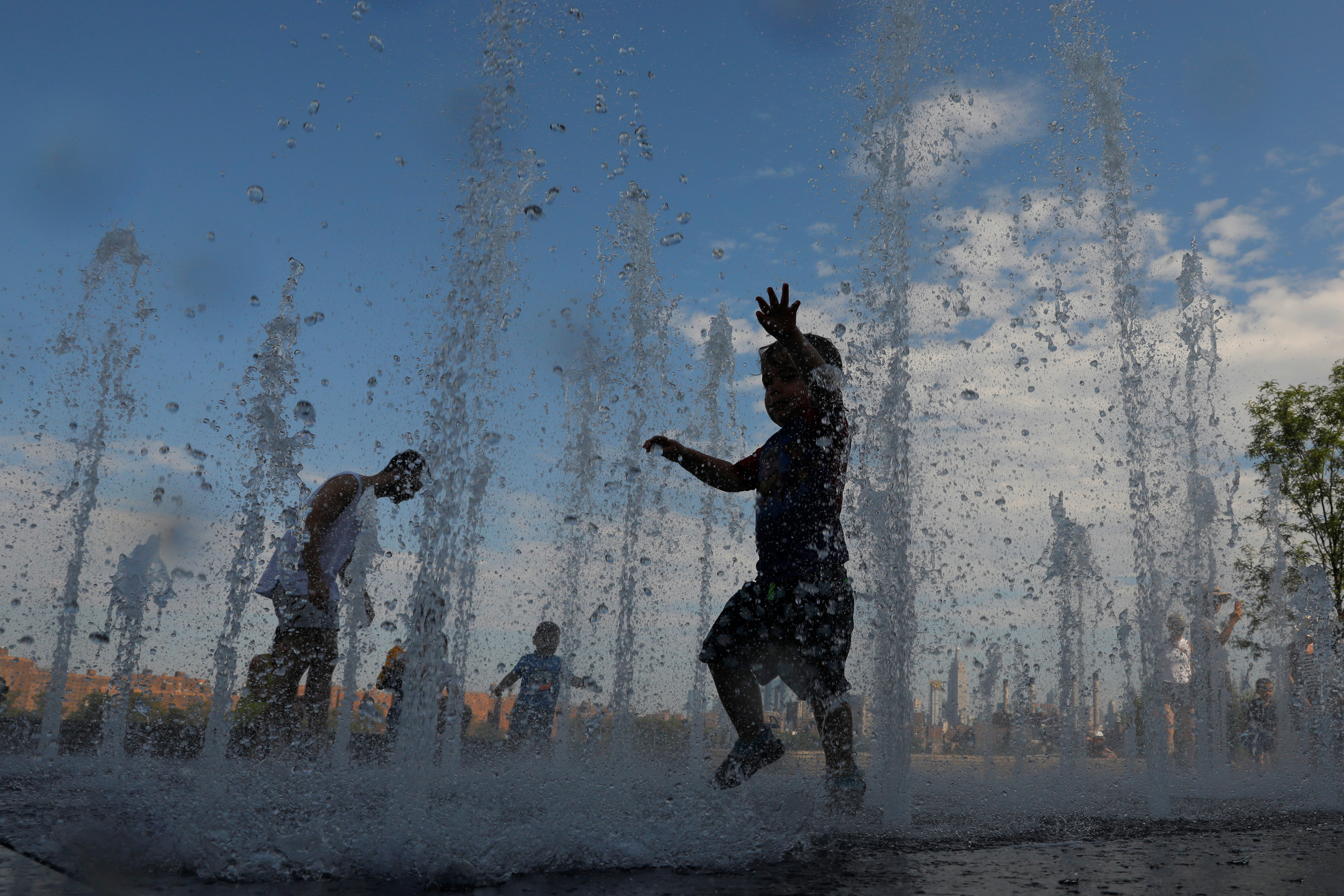 Children play in a water feature in Domino Park as a heatwave continued to affect the region in Brooklyn, New York City, New York, U.S., July 21, 2019. REUTERS/Andrew Kelly - RC191CC104E0