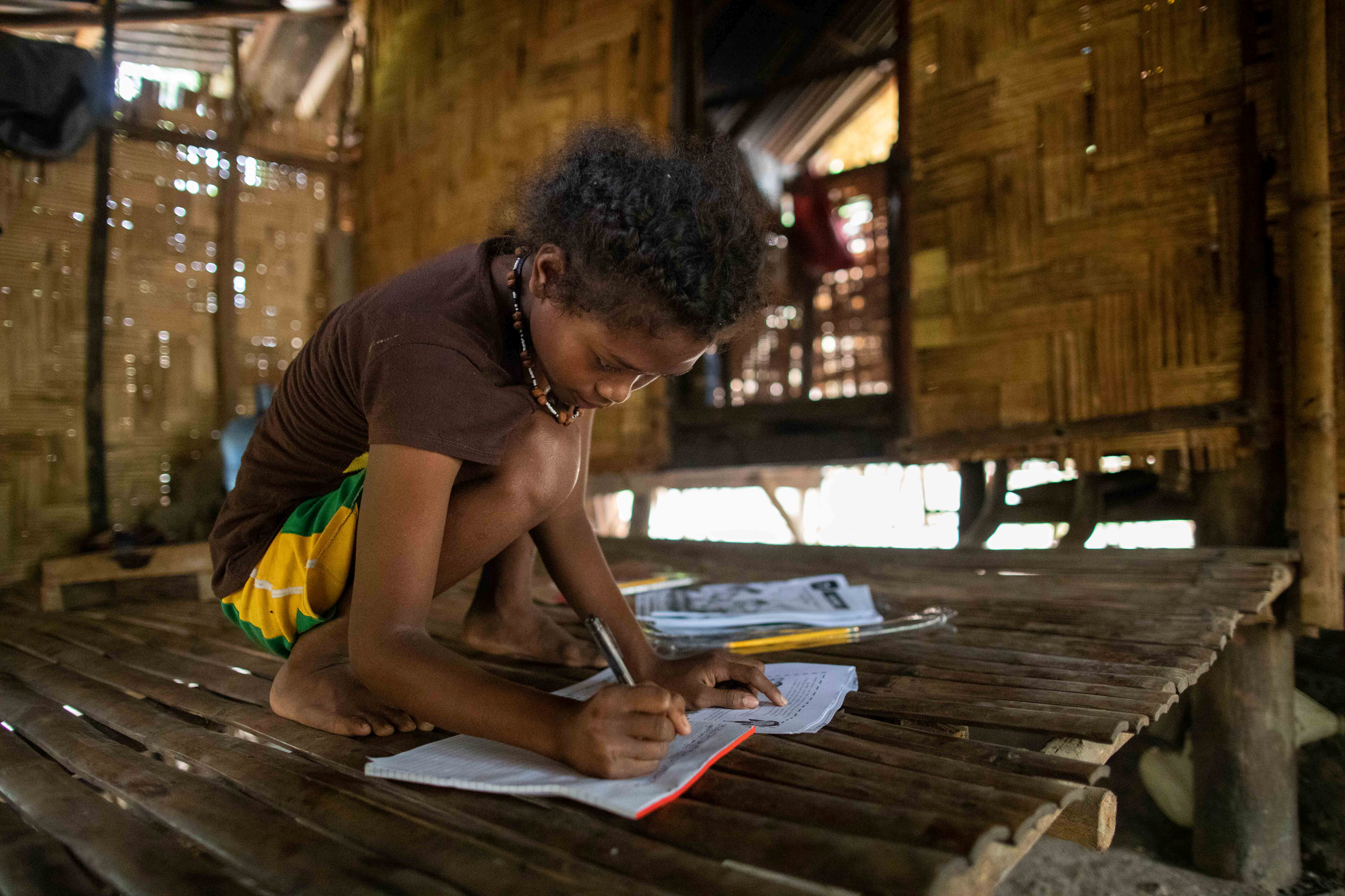 Seventh grade student Abigail Sibal, 13, works on her modules at home after attending a session at the makeshift rickshaw distance learning center for the Aeta community in Porac, Pampanga, Philippines, October 12, 2020. REUTERS/Eloisa Lopez - RC2VIJ9ZFYD3