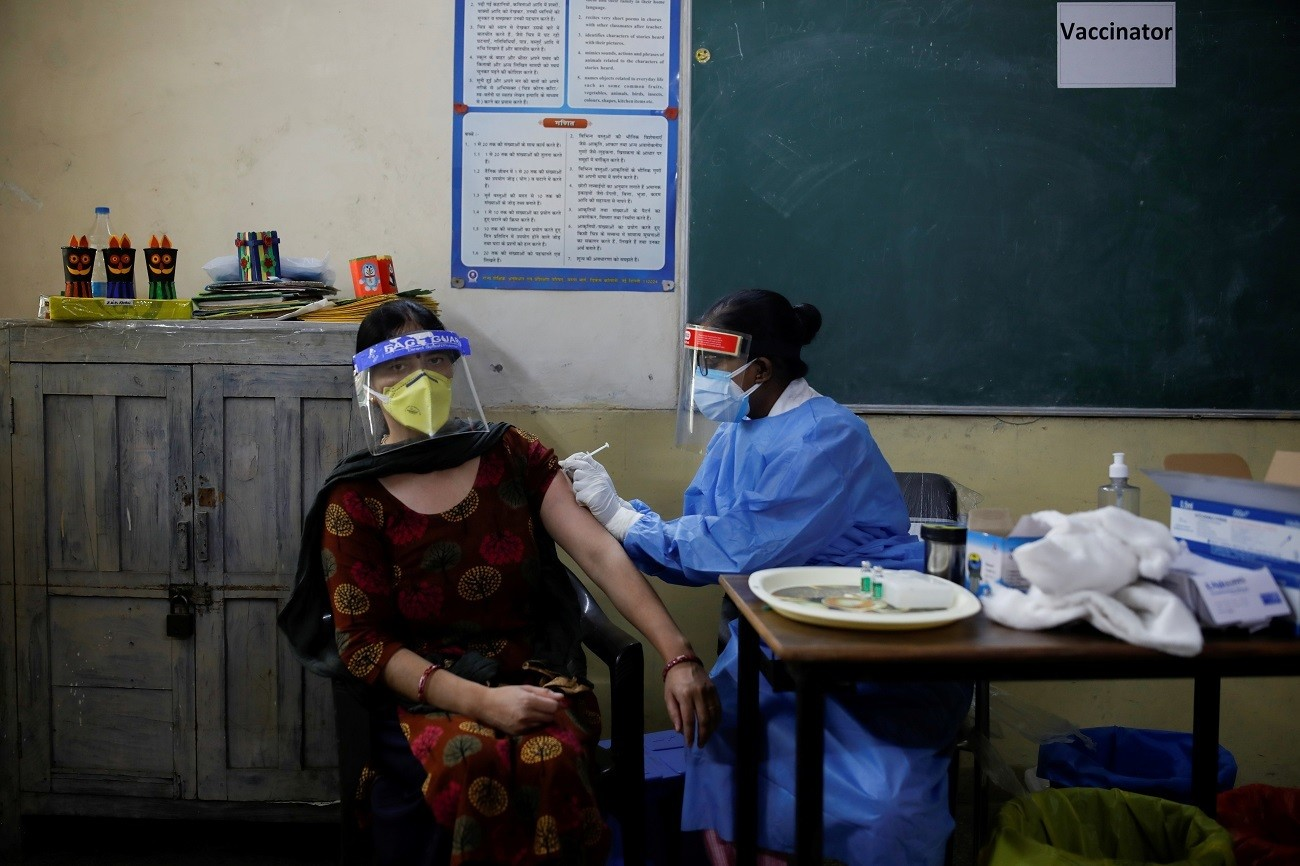 A healthcare worker gives a dose of COVISHIELD, a coronavirus disease (COVID-19) vaccine manufactured by Serum Institute of India, to a woman inside a classroom of a school, which has been converted into a temporary vaccination centre, in New Delhi, India, May 4, 2021. REUTERS/Adnan Abidi     TPX IMAGES OF THE DAY - RC2S8N9W7B1K