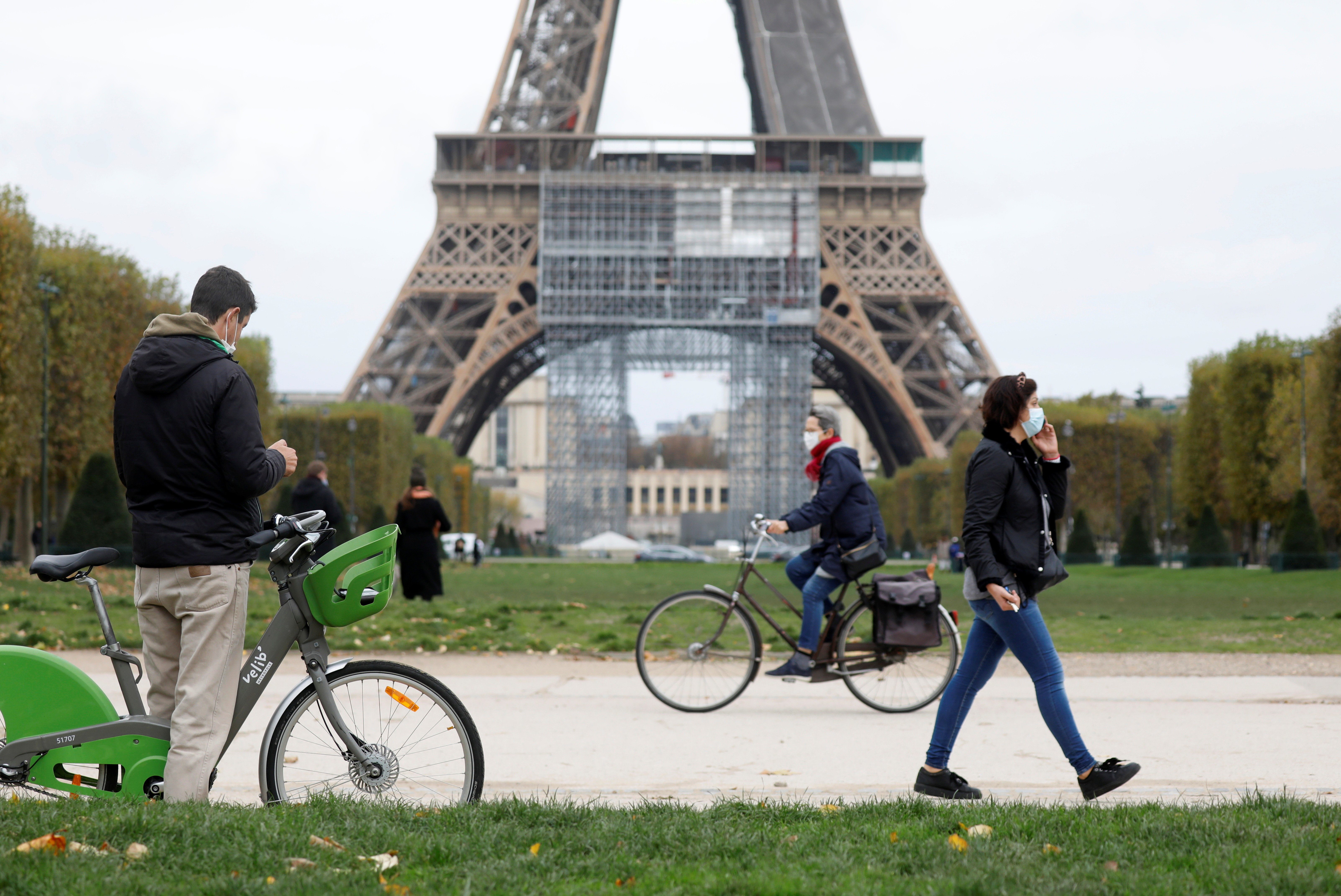 People pass by the Eiffel Tower before the national lockdown introduced as part of the new COVID-19 measures to fight a second wave of the coronavirus disease, in Paris, France, October 29, 2020.   REUTERS/Charles Platiau - RC2ESJ9E8LAO