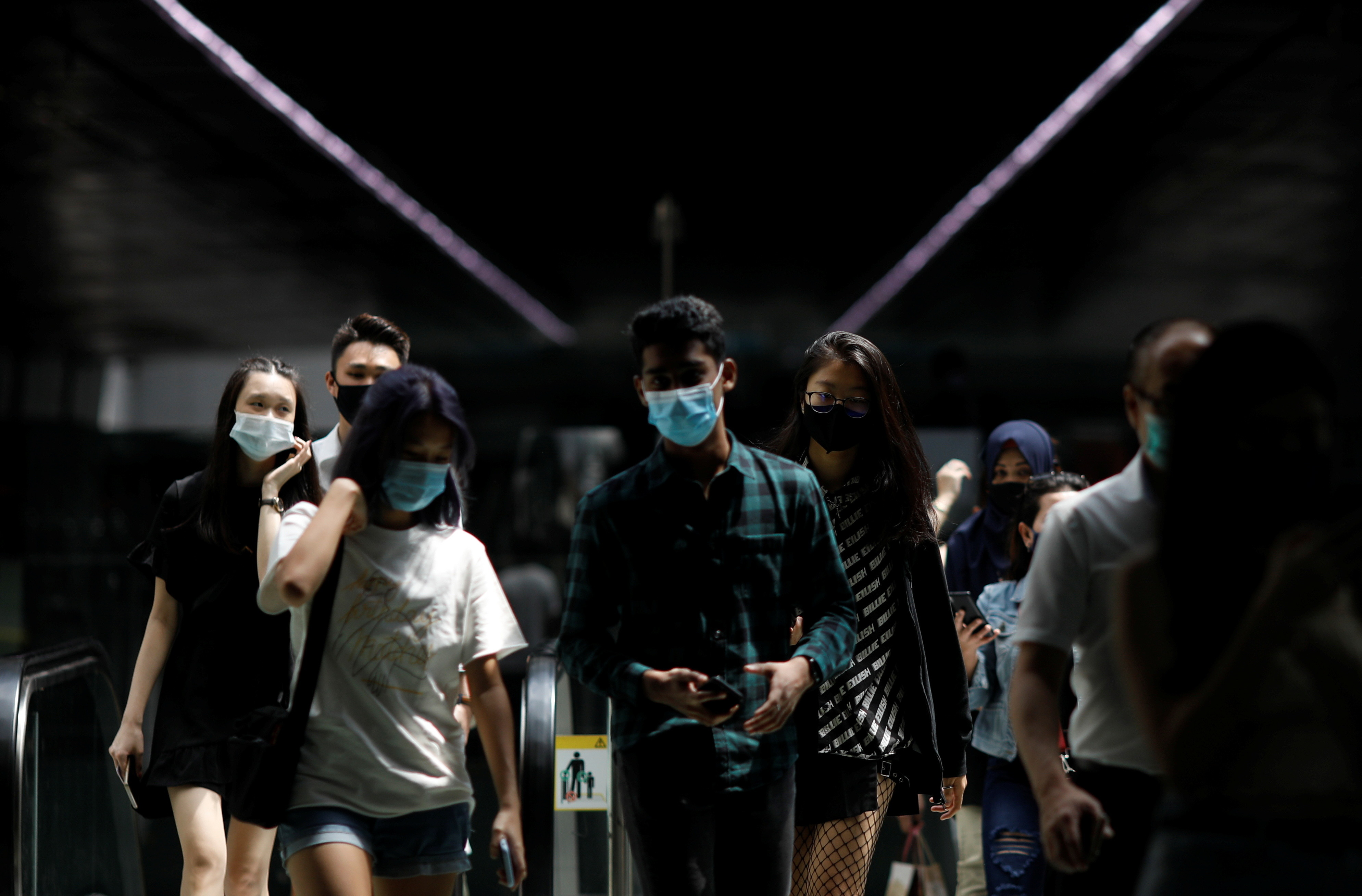 People wearing face masks leave a train station in Singapore December 8, 2020.  REUTERS/Edgar Su - RC2WIK94ELKO