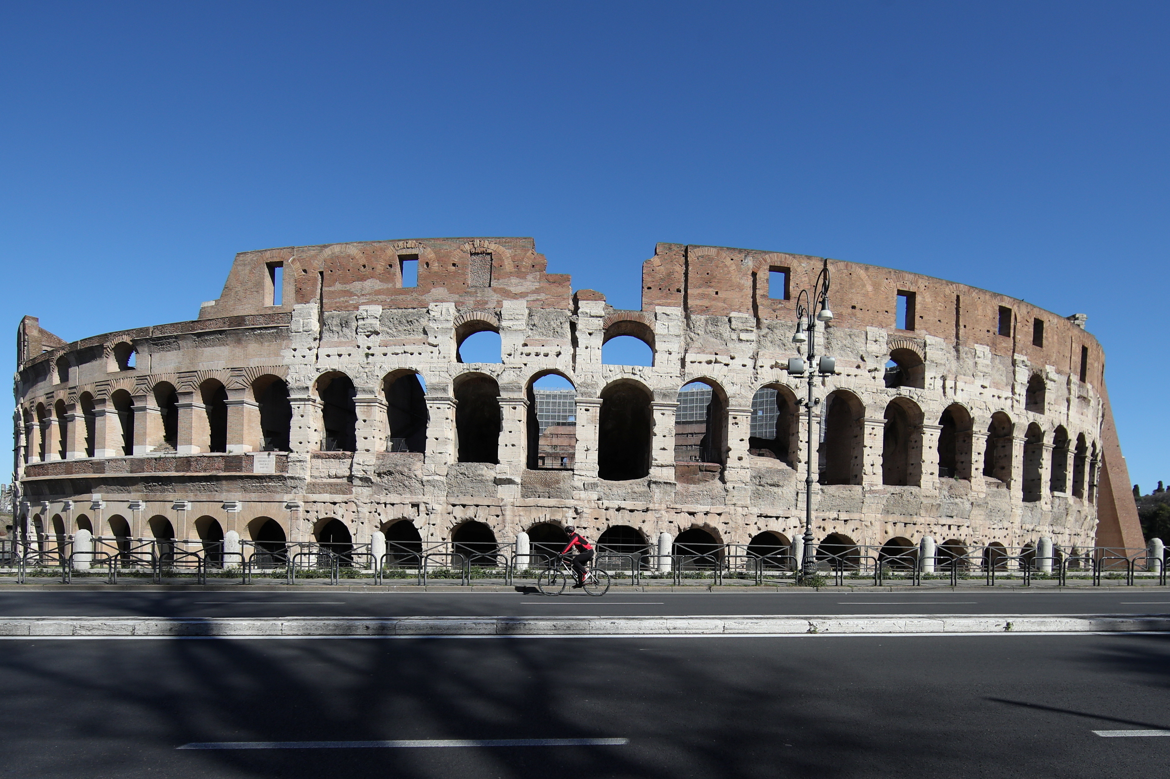 A person rides a bike in front of the Colosseum as Rome becomes a 'red zone', going into lockdown, as the country struggles to reduce the coronavirus disease (COVID-19) infections, in Rome, Italy, March 15, 2021. REUTERS/Yara Nardi - RC2MBM9LJI0U