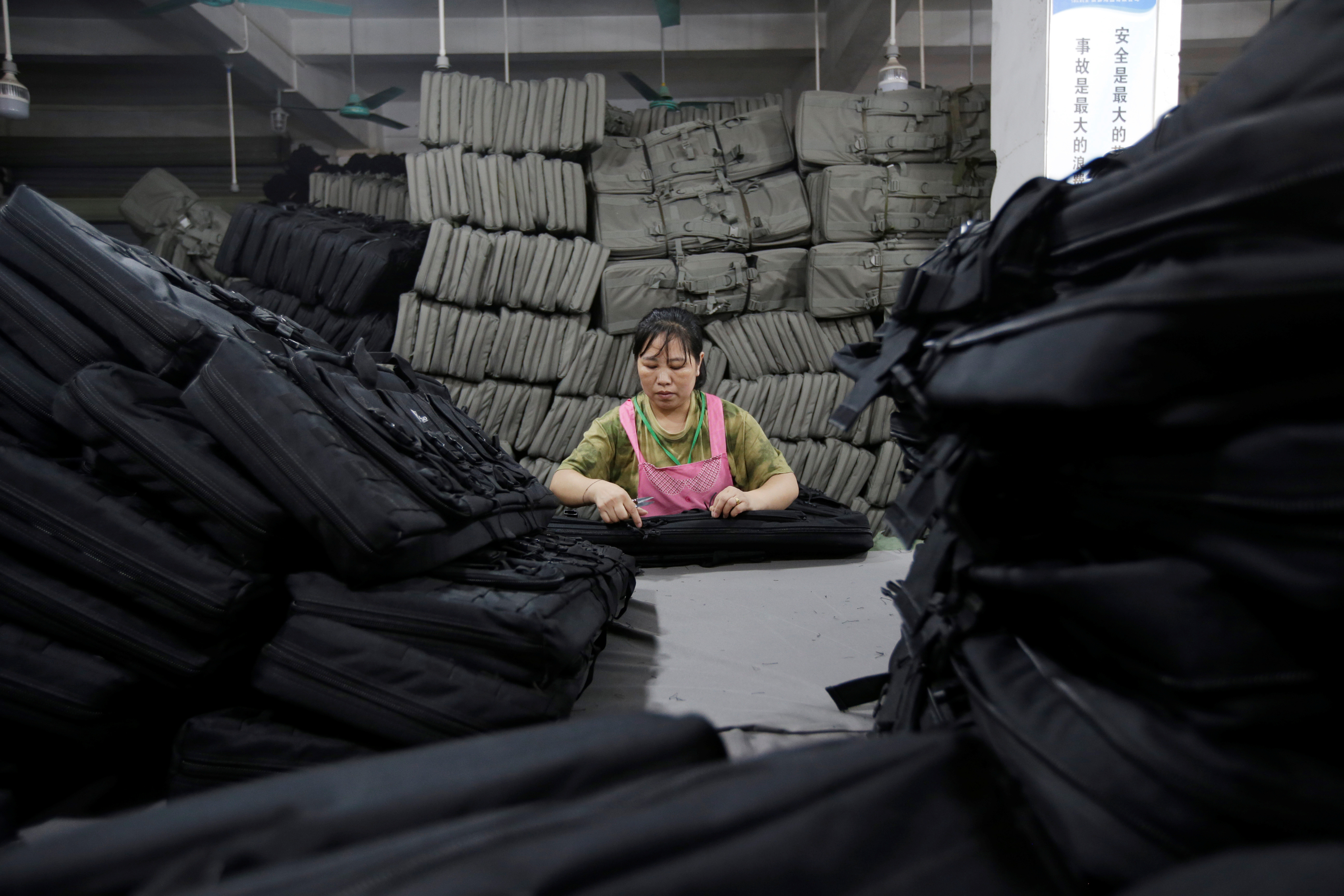 A woman works on gun cases in a factory of firearm equipment manufacturer Yakeda Tactical Gear Co, which exports most of its products to the United States, in Guangzhou, Guangdong province, China June 1, 2019. Picture taken June 1, 2019. REUTERS/Jason Lee? - RC11B43C1550