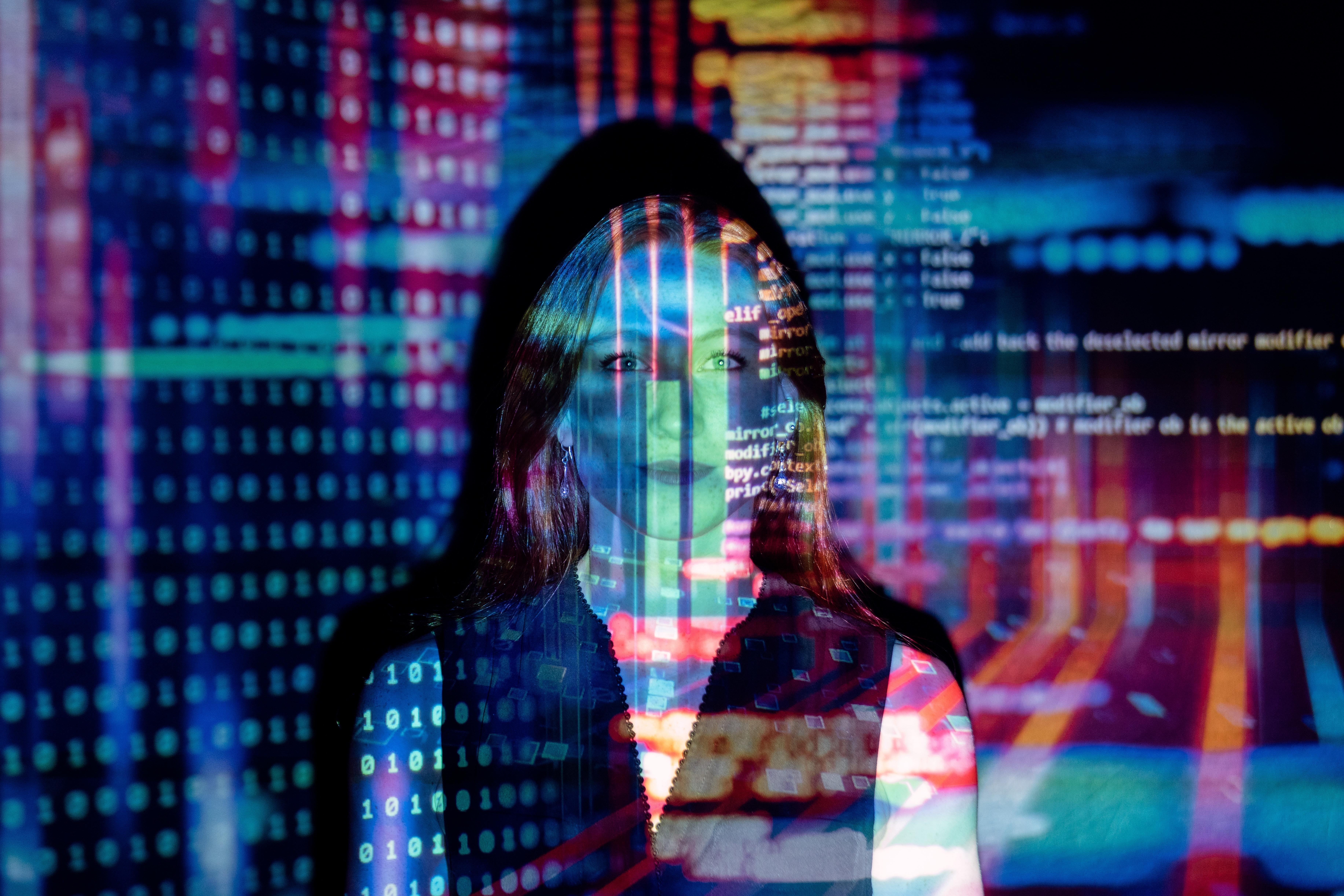 Woman, colourful computer code; AI technology development.
