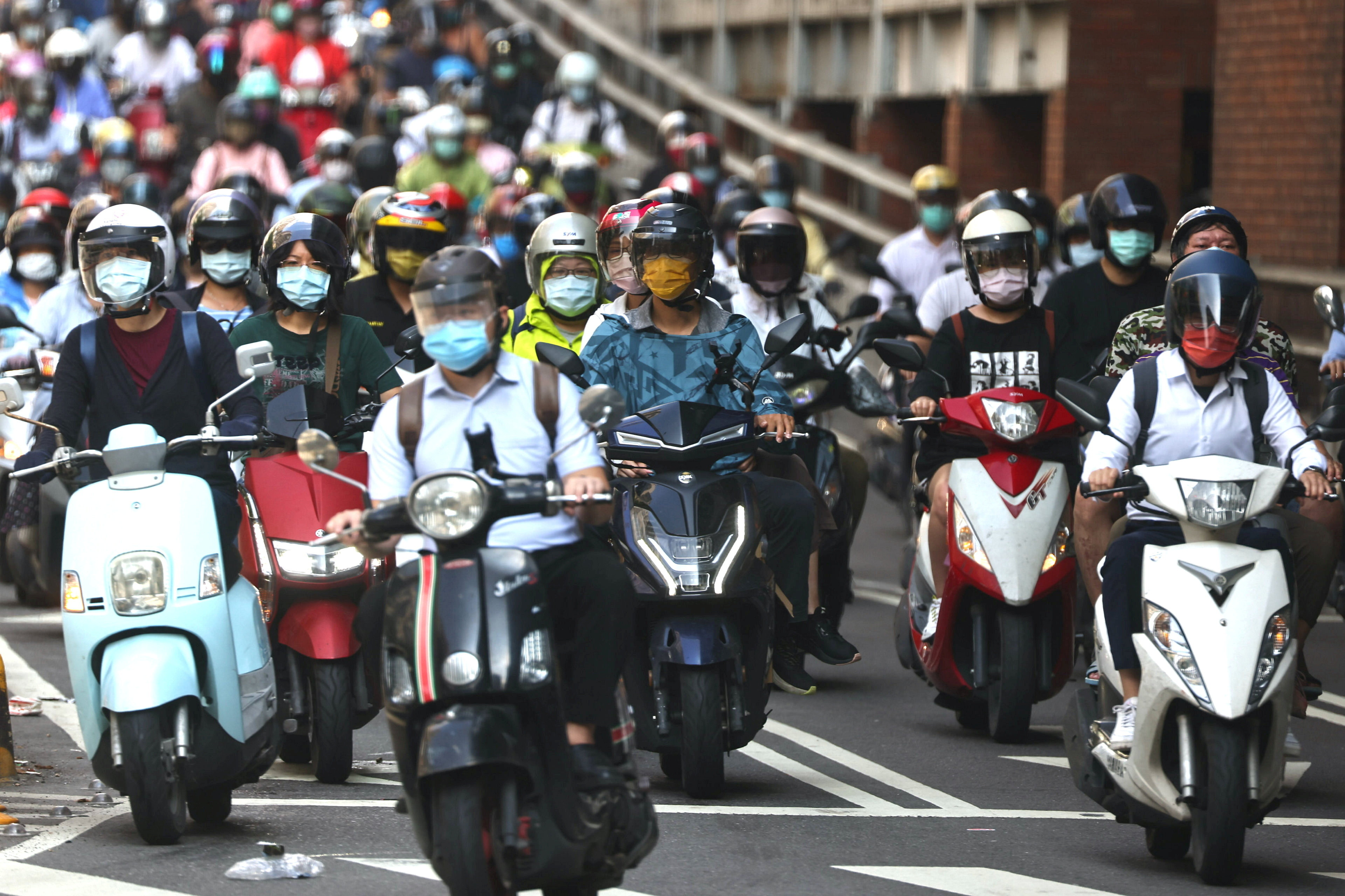 Commuters wear face masks to protect themselves from the coronavirus disease (COVID-19) during morning rush hour after Taiwan Central Epidemic Command Center (CECC) ease up coronavirus disease (COVID-19) Level 3 restrictions in Taipei, Taiwan, July 13, 2021. REUTER/Ann Wang - RC2CJO9UVQOV