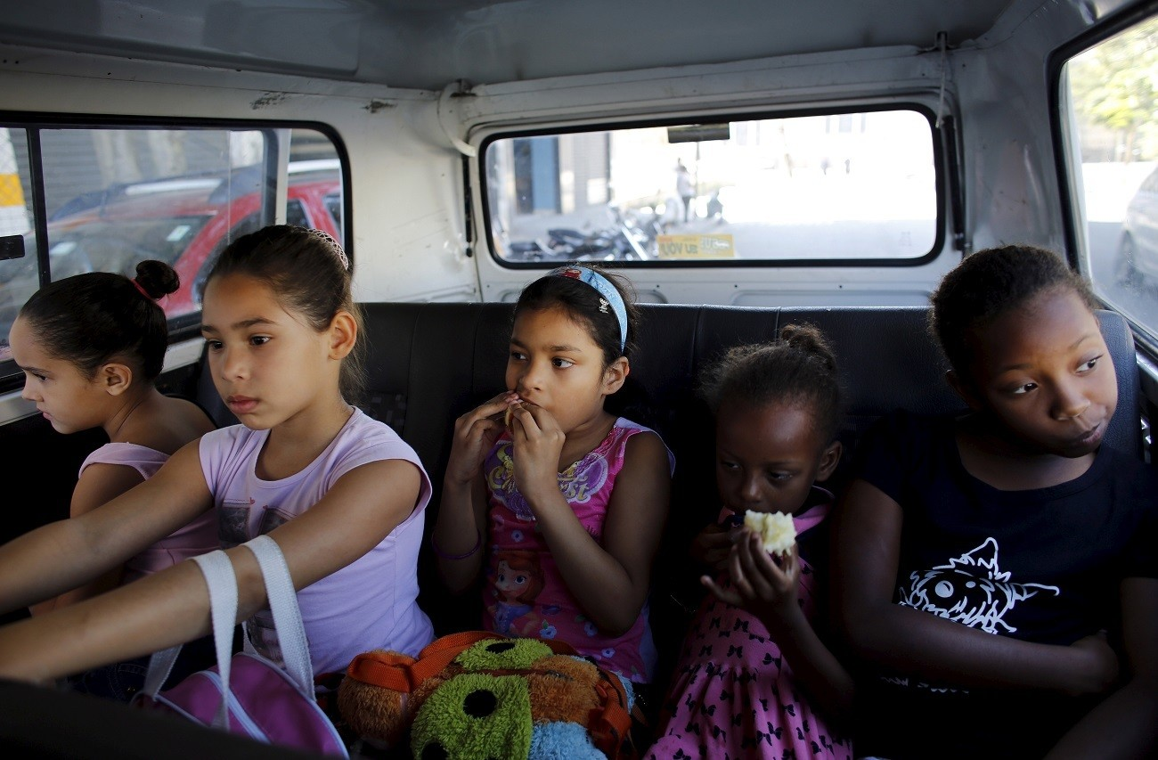 """Young girls ride a van to their ballet lesson at the New Dreams dance studio, passing through the rough Luz neighborhood known to locals as Cracolandia (Crackland), in Sao Paulo, Brazil, August 14, 2015. For the young girls learning to jump and plie, the dance studio provides a way forward and out of the difficult environment they have grown up in. Brazil is one of the world's highest consuming countries of crack cocaine, and Cracolandia, or """"Crack Land"""", located in the outskirts of Sao Paulo, is one of the most intense and brutal hubs. Picture taken August 14, 2015. REUTERS/Nacho Doce - GF10000175037"""