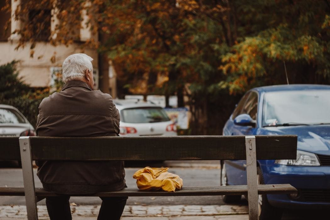 Image of elderly person sitting along