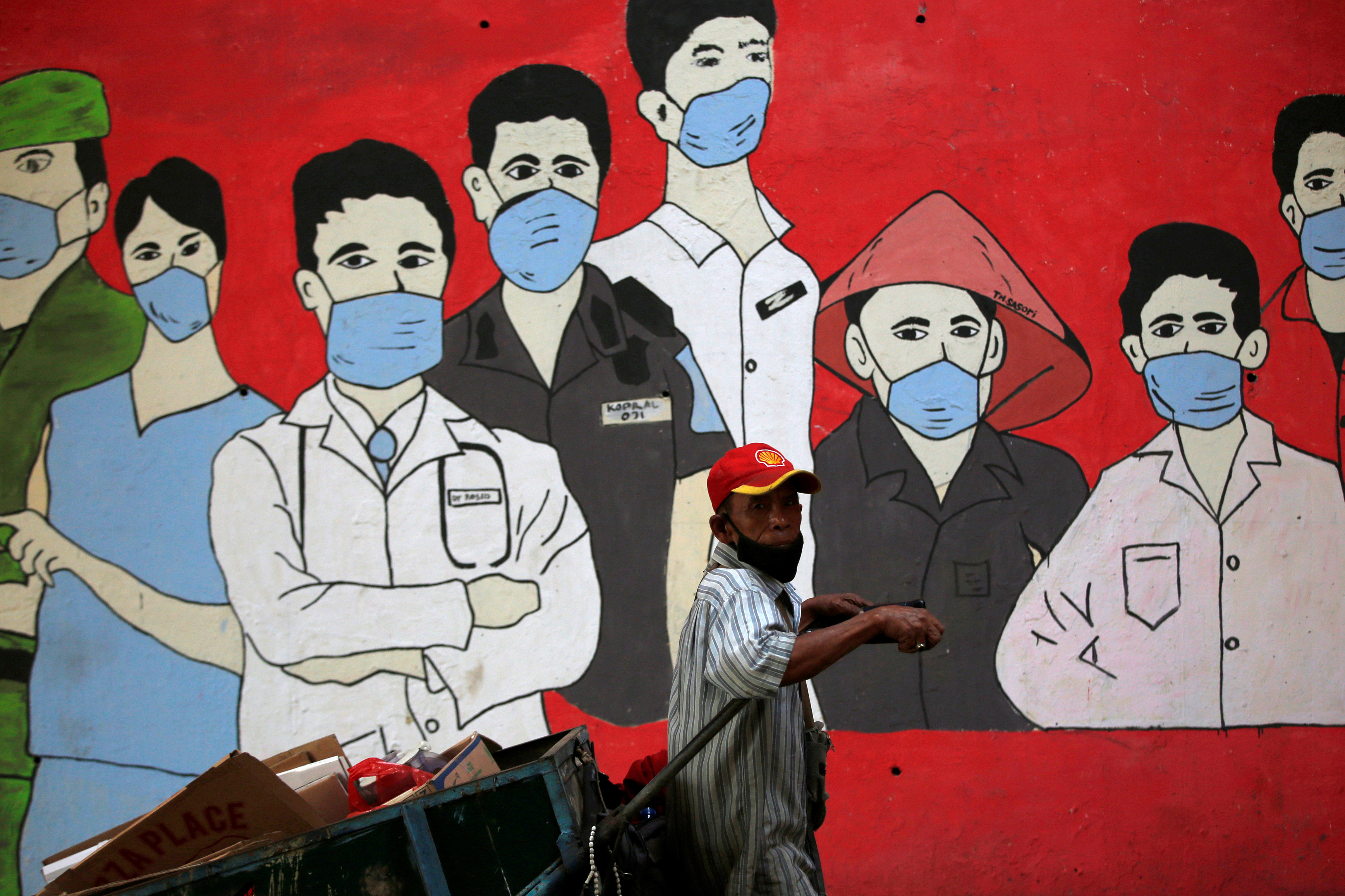A man wearing a protective mask pulls a cart past a mural supporting frontline workers as the coronavirus disease (COVID-19) outbreak continues in Jakarta, Indonesia, September 8, 2020. REUTERS/Willy Kurniawan - RC23UI9QCKMW