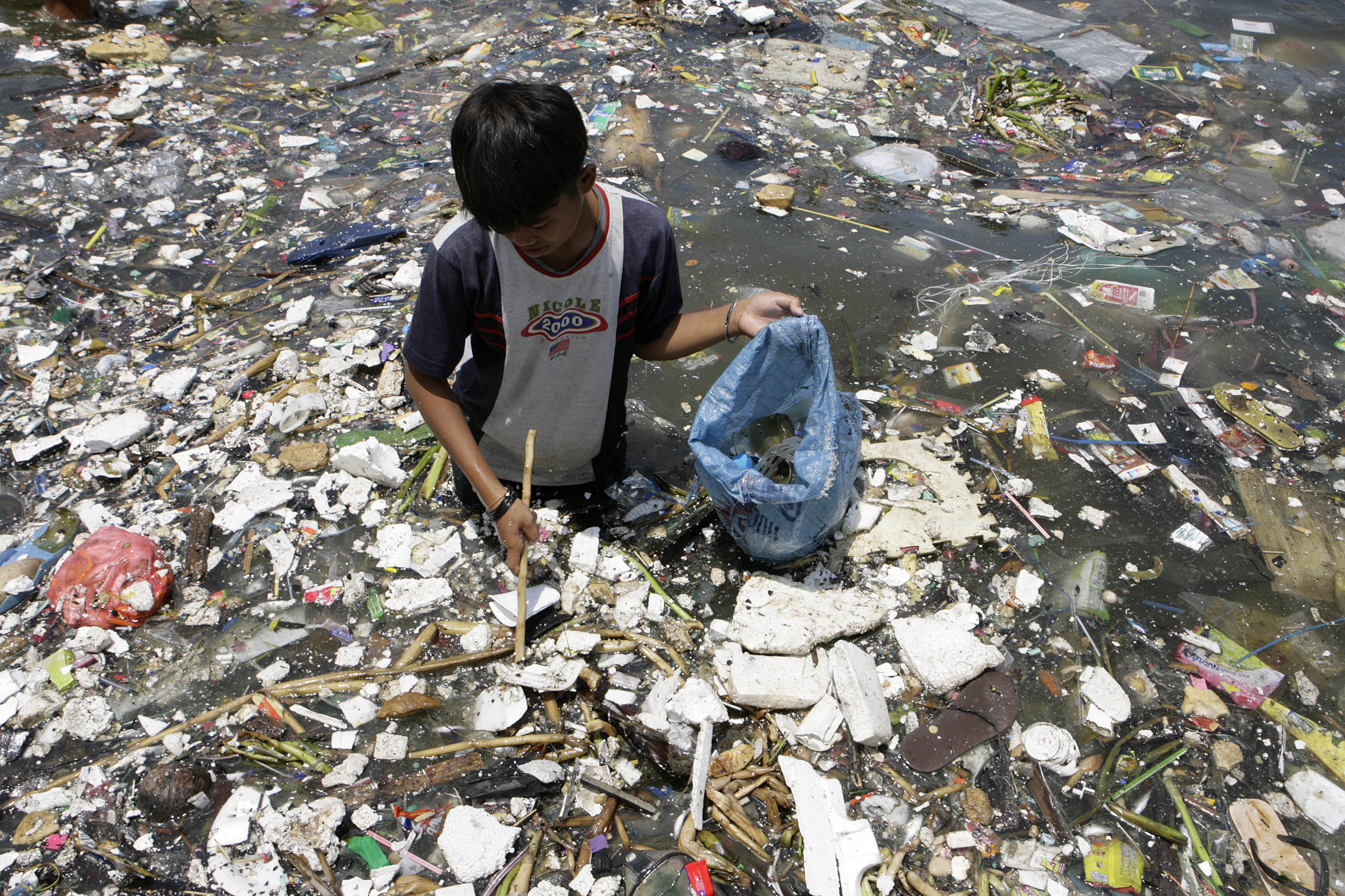 A boy collects plastic materials near a polluted coastline to sell in Manila