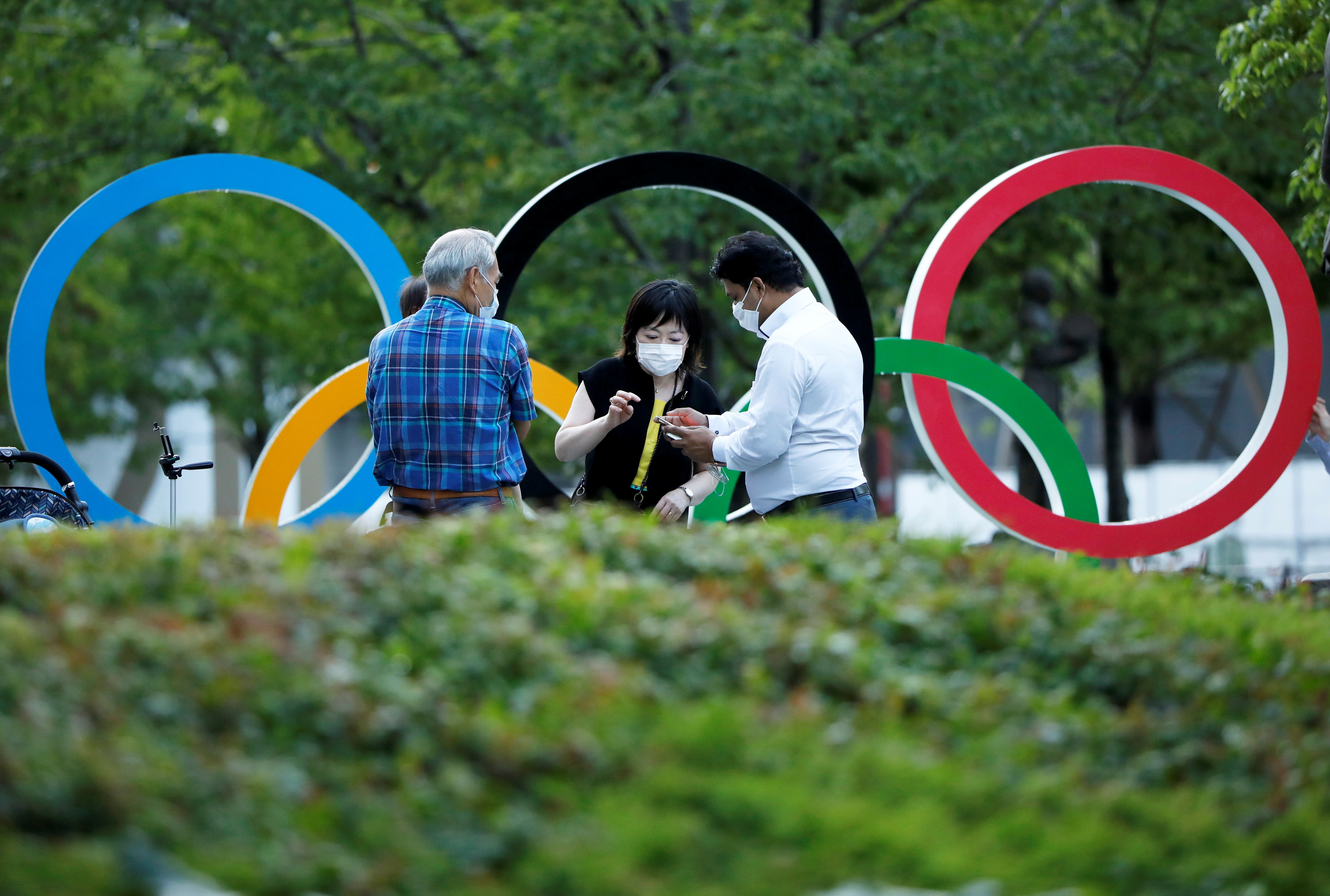 People chat next to Olympic Rings monument outside the Japan Olympic Committee (JOC) headquarters near the National Stadium, the main stadium for the 2020 Tokyo Olympic Games that have been postponed to 2021 due to the COVID-19 pandemic, in Tokyo, June 23, 2021 on the day to mark one month to go until the opening of the Olympic Games.  REUTERS/Issei Kato - RC296O9SBN01