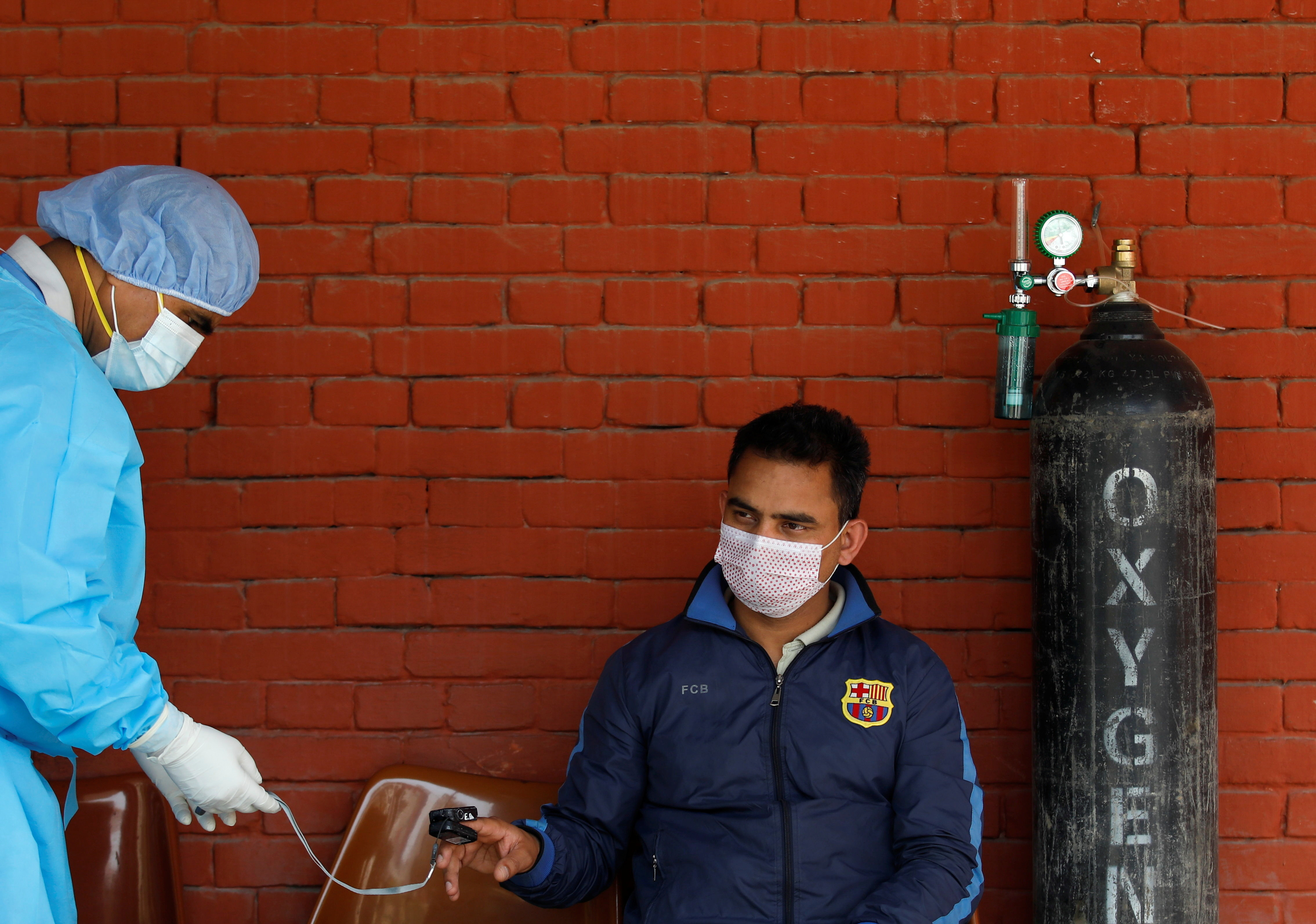 A doctor checks the oxygen level of a man suffering from coronavirus disease (COVID-19) as he sits outside an emergency room waiting to get admitted amid the lack of free beds at the hospital as the major second coronavirus wave surges in Kathmandu, Nepal April 30, 2021. REUTERS/Navesh Chitrakar - RC256N9NXBX9