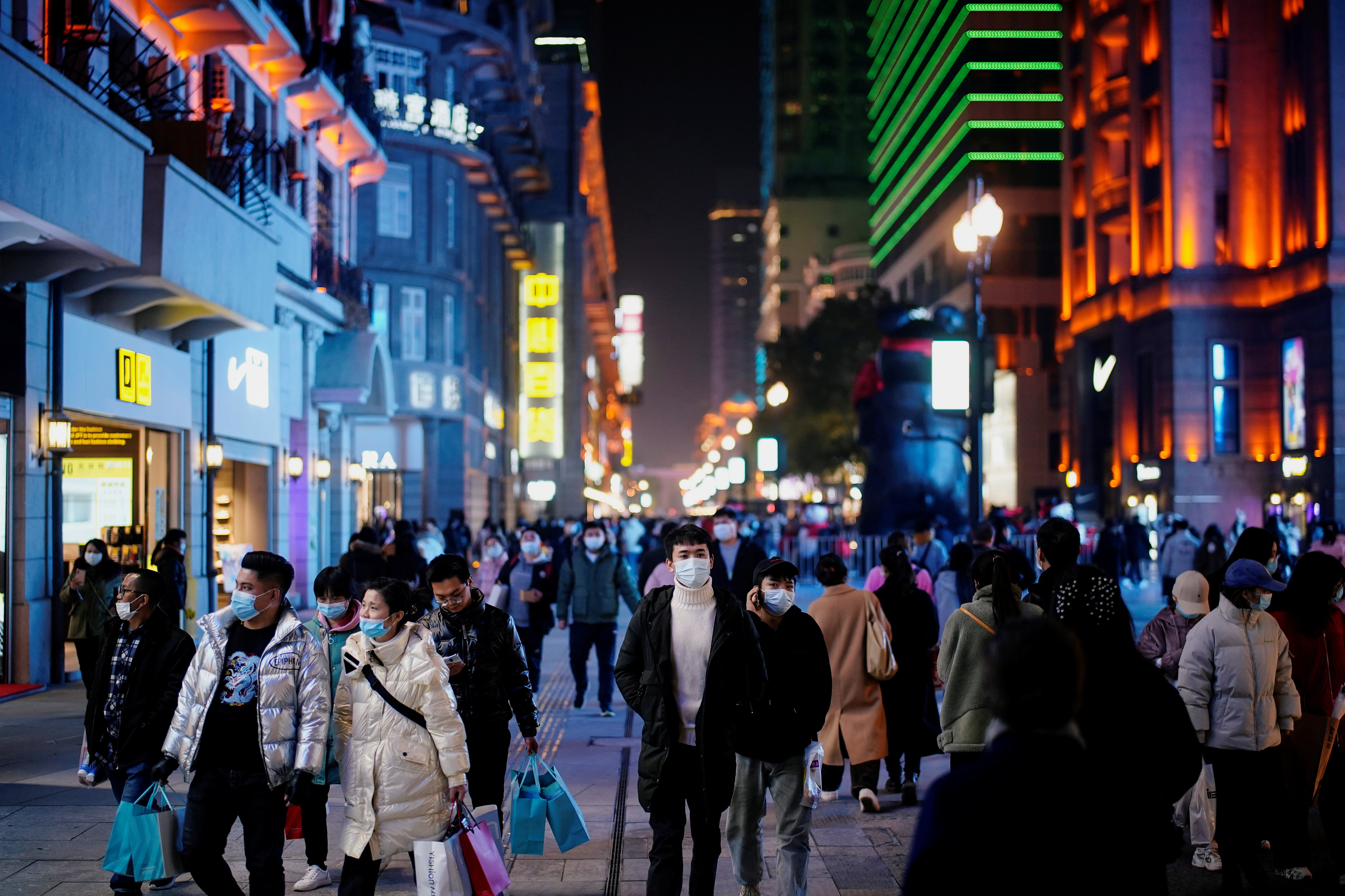 People wearing face masks are seen at a main shopping area almost a year after the global outbreak of the coronavirus disease (COVID-19) in Wuhan, Hubei province, China December 7, 2020. Picture taken December 7, 2020. REUTERS/Aly Song - RC2UIK9UPBQF