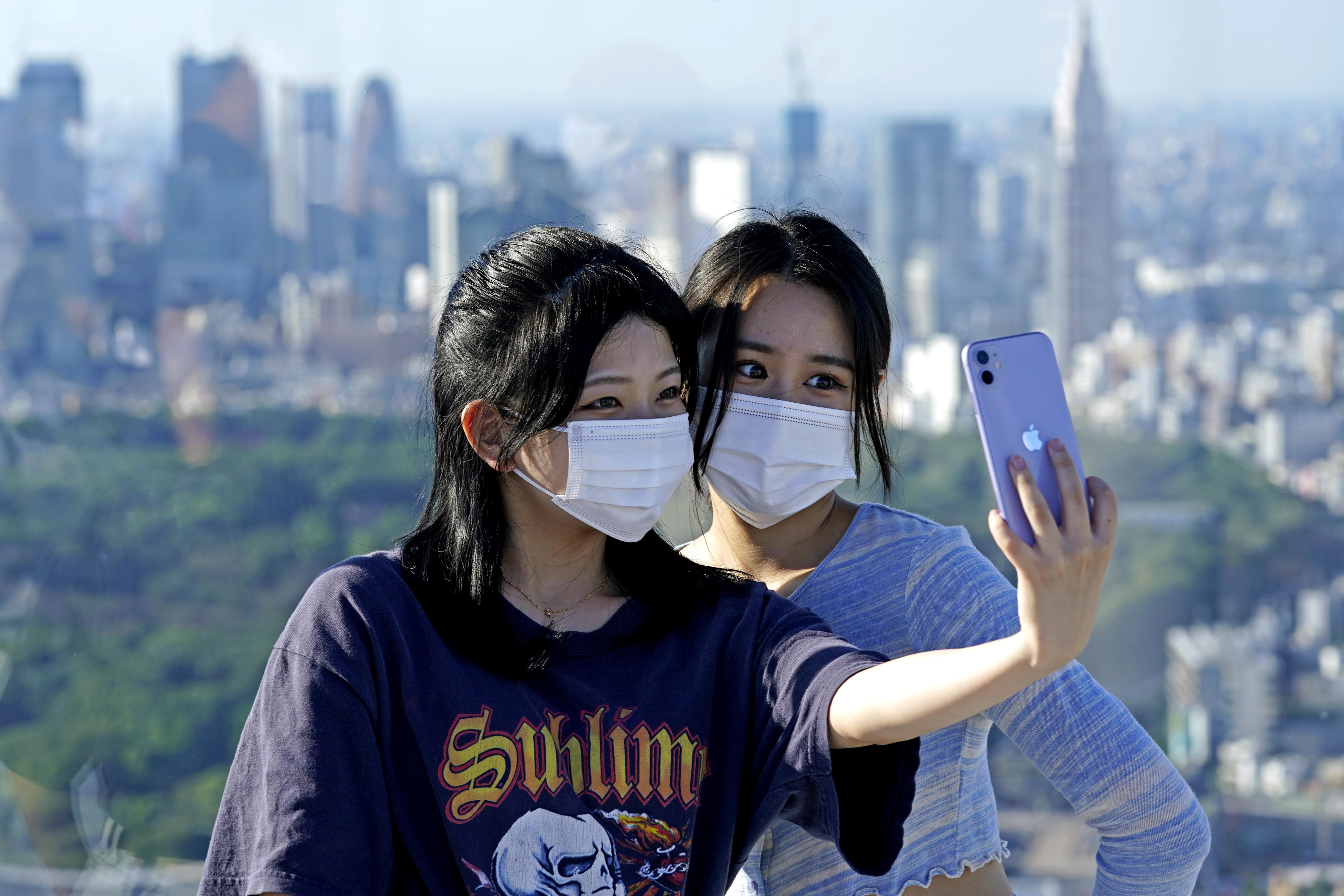 Two women take a selfie using a smartphone from a viewing deck overlooking a city skyline.