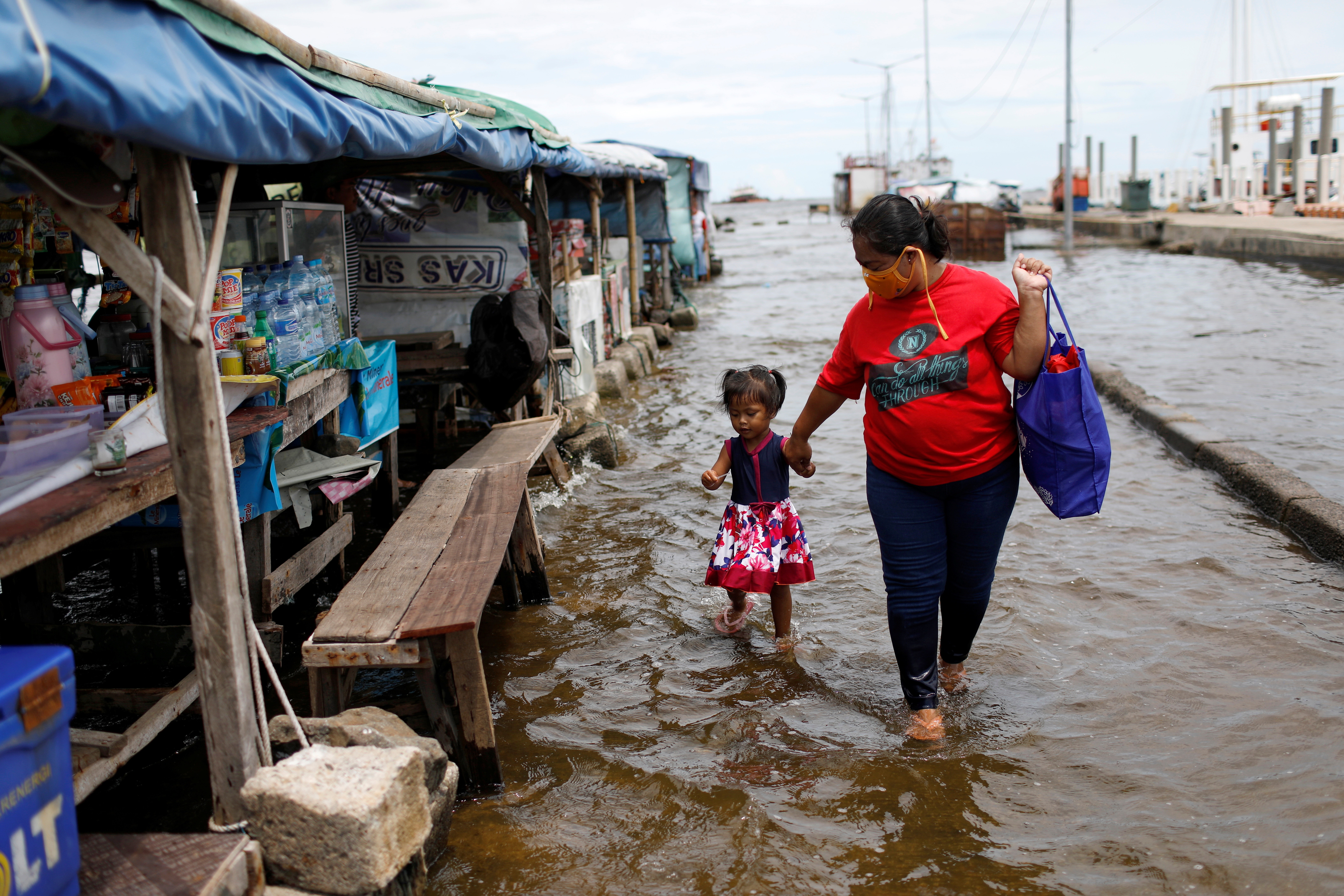 Evi, a 35-years-old vendor, walks with her 2-years-old daughter through water at Kali Adem port, which is impacted by high tides due to the rising sea level and land subsidence, north of Jakarta, Indonesia November 20, 2020. REUTERS/Willy Kurniawan - RC2Z6K91NY4N