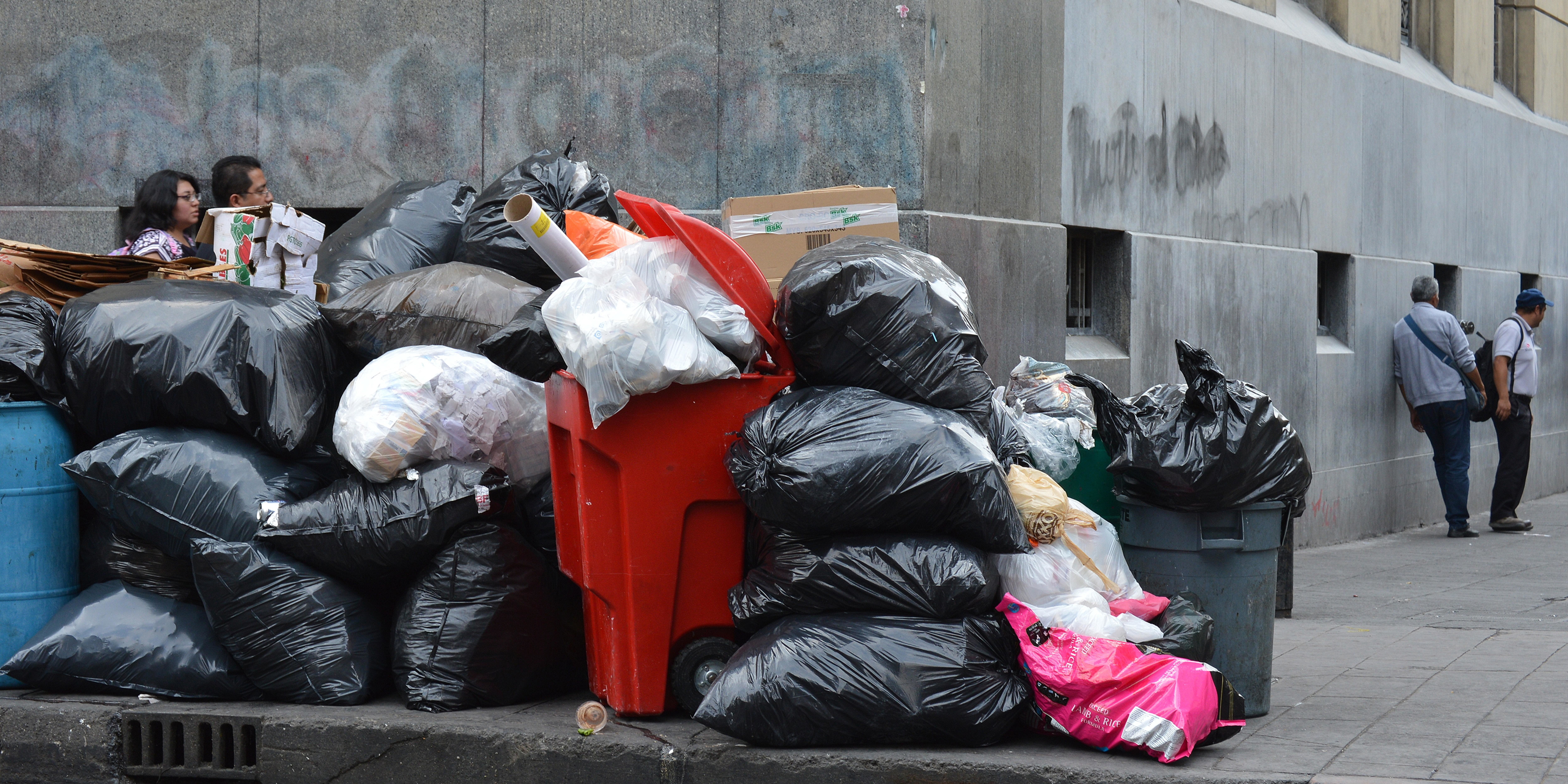 Rubbish and waste piling up at the side of a street.