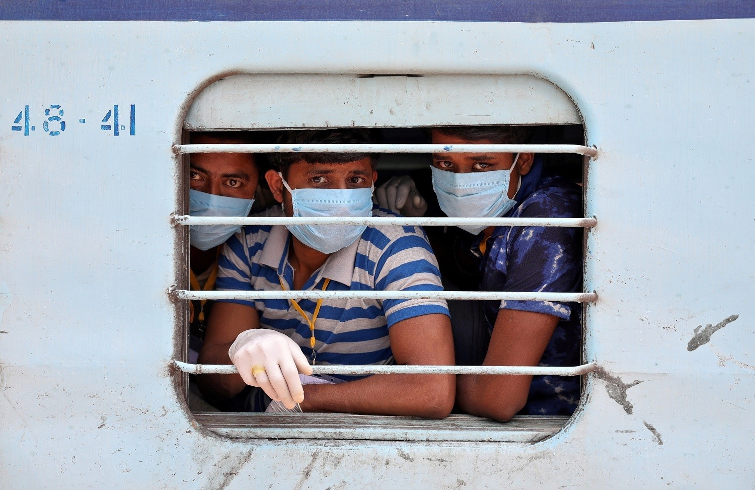 Migrant workers, who were stranded in the western state of Rajasthan due to a lockdown imposed by the government to prevent the spread of coronavirus disease (COVID-19), wear protective masks as they look out from a window of a train upon their arrival in their home state of eastern West Bengal, at a railway station on the outskirts of Kolkata, India, May 5, 2020. REUTERS/Rupak De Chowdhuri     TPX IMAGES OF THE DAY - RC27IG9ICJTR