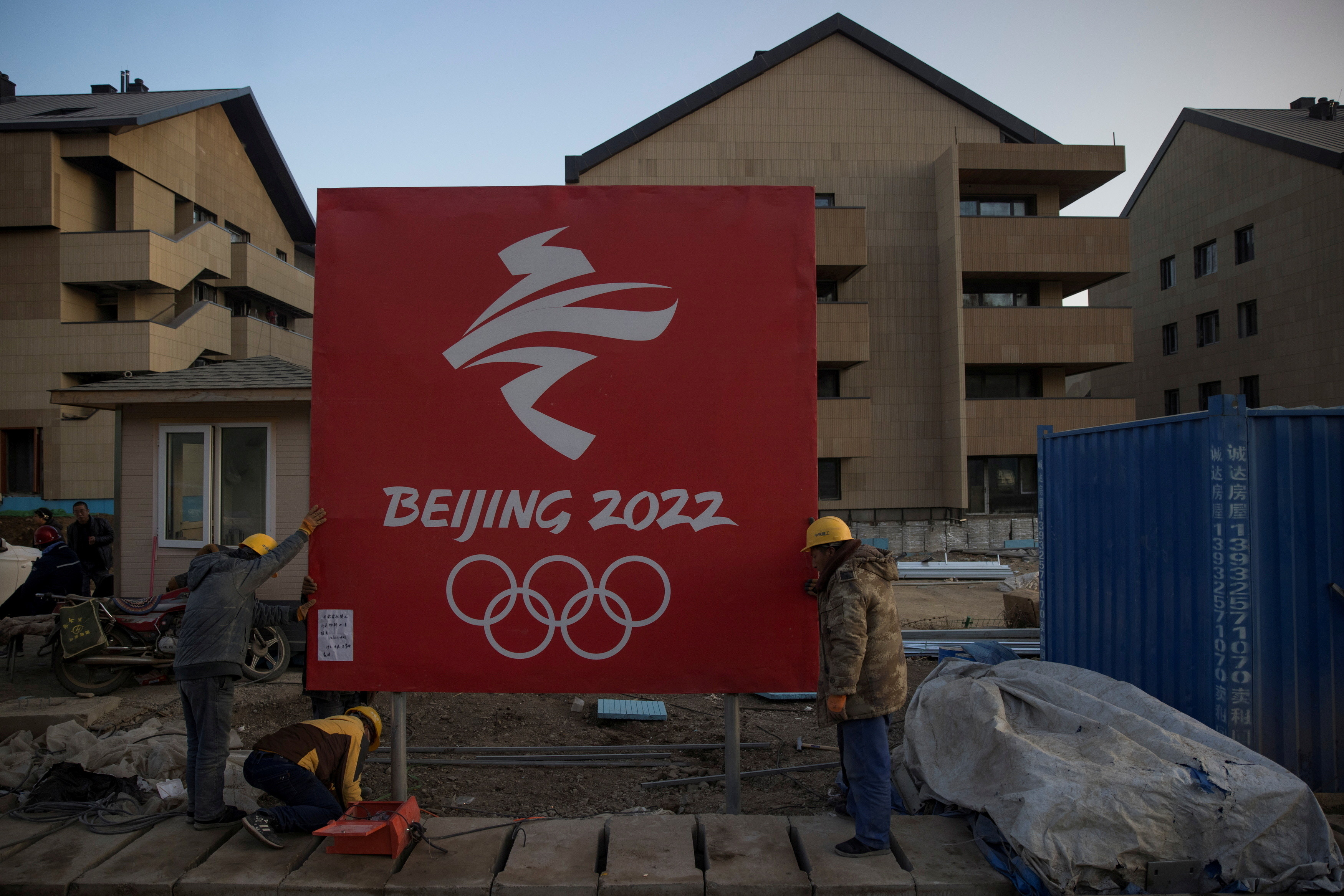 Workers move a sign at the Olympic Village for the 2022 Winter Olympics in the Chongli district of Zhangjiakou, Hebei province, China, October 29, 2020.