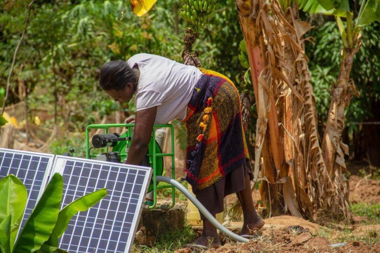 A Kenyan farmer sets up her solar irrigation pump in Busia county, Kenya on February, 2019.