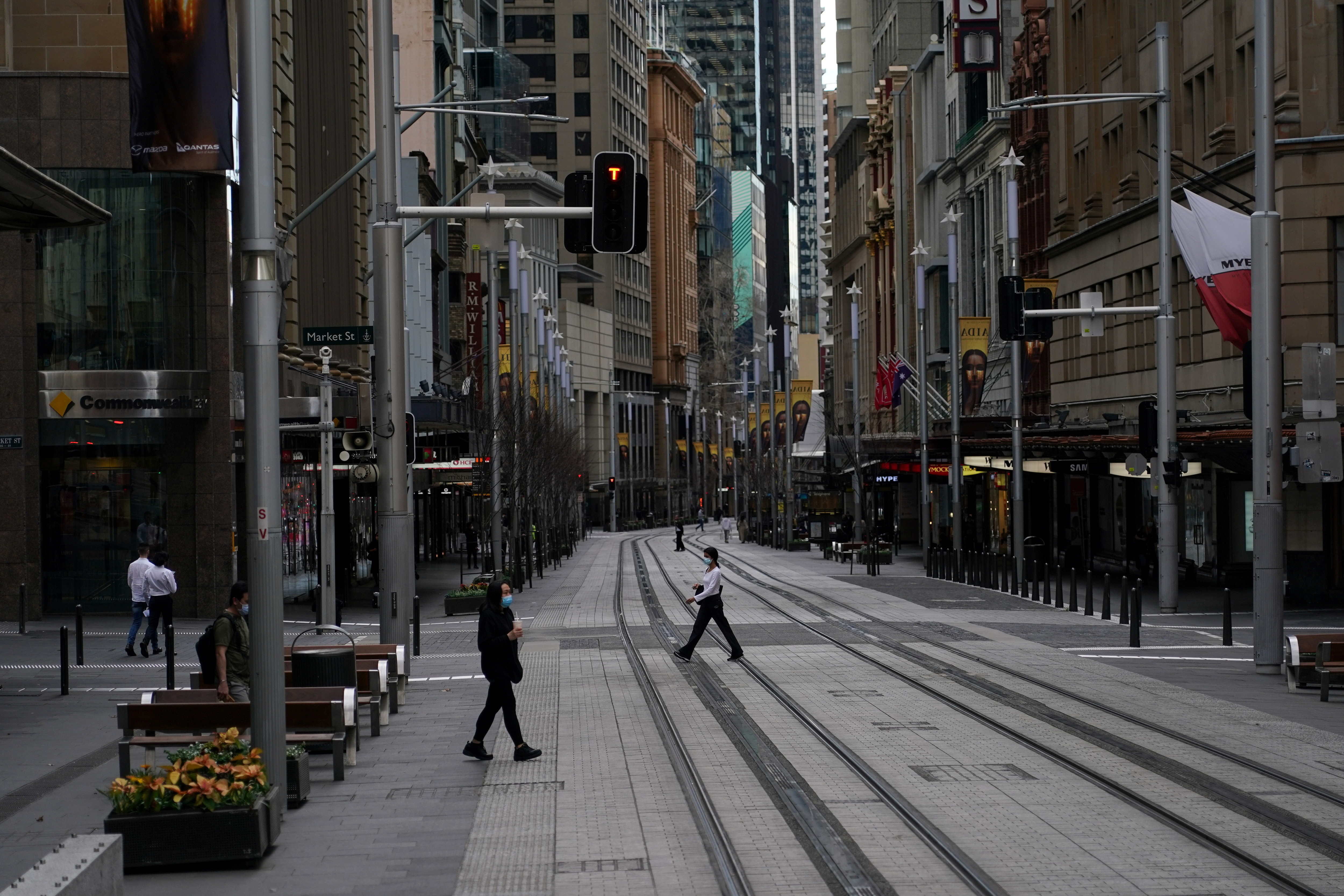 People in protective face masks walk through the quiet city centre during a lockdown to curb the spread of a coronavirus disease (COVID-19) outbreak in Sydney, Australia, July 28, 2021.  REUTERS/Loren Elliott - RC2HTO9R8XP3