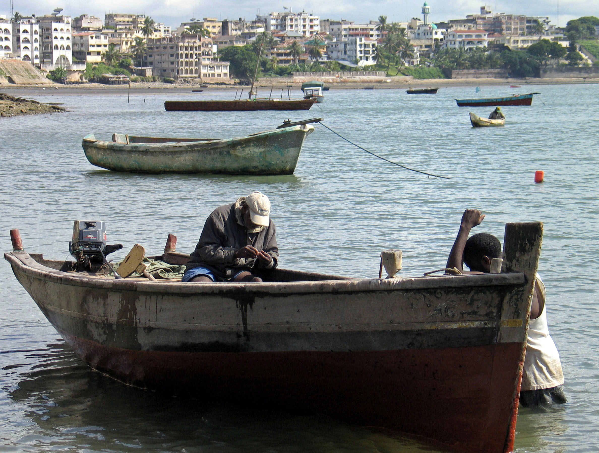 image of Kenyan fishermen sitting in their boats in the port of Mombasa Old Town, Kenya
