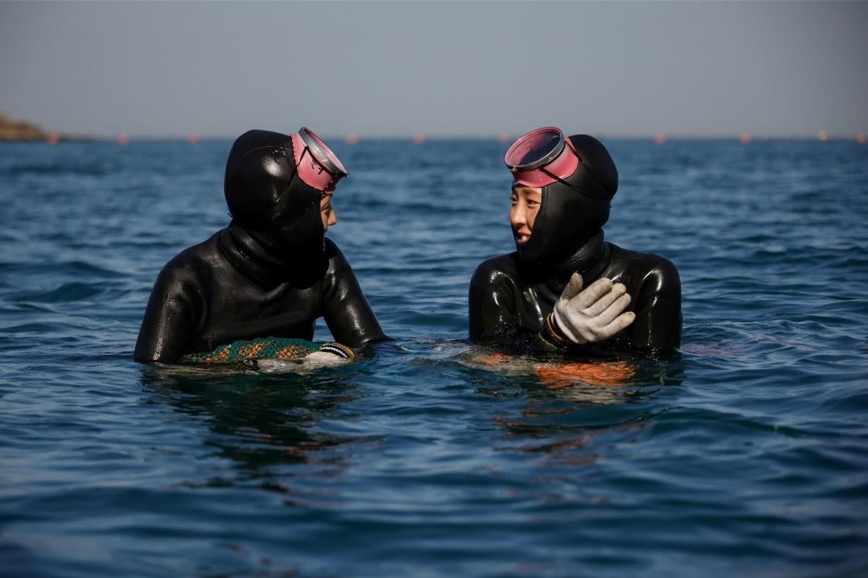 Jin and Woo, two 'sea women' talk in the sea.