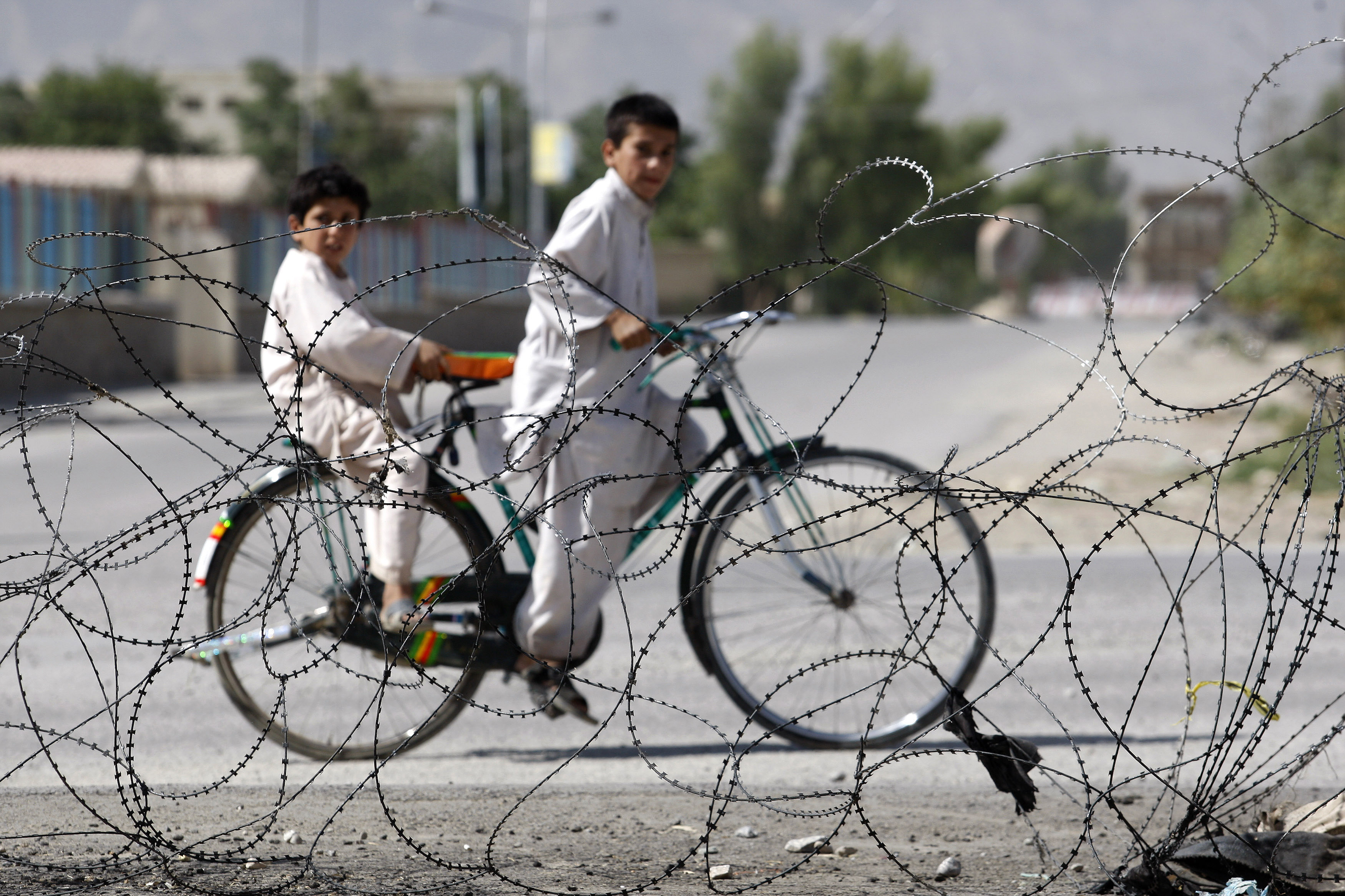Afghan children ride a bicycle in front of a police station in the center of Kandahar city