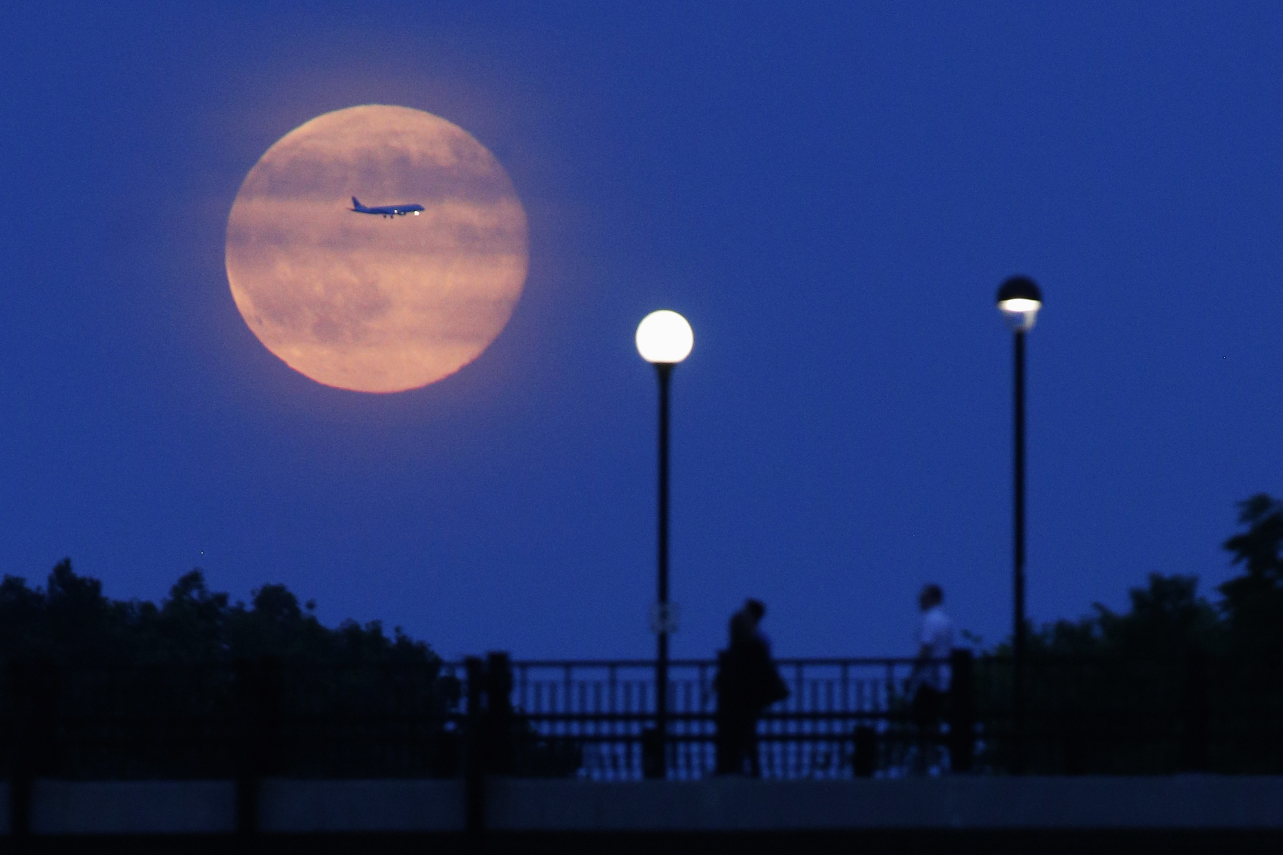 Aircraft passes in front of a Supermoon rising over the Rideau Canal in Ottawa July 12, 2014. Occurring when a full moon or new moon coincides with the closest approach the moon makes to the Earth, the Supermoon results in a larger-than-usual appearance of the lunar disk.    REUTERS/Blair Gable (CANADA - Tags: SOCIETY TRANSPORT ENVIRONMENT TPX IMAGES OF THE DAY) - GM1EA7D0SBK01