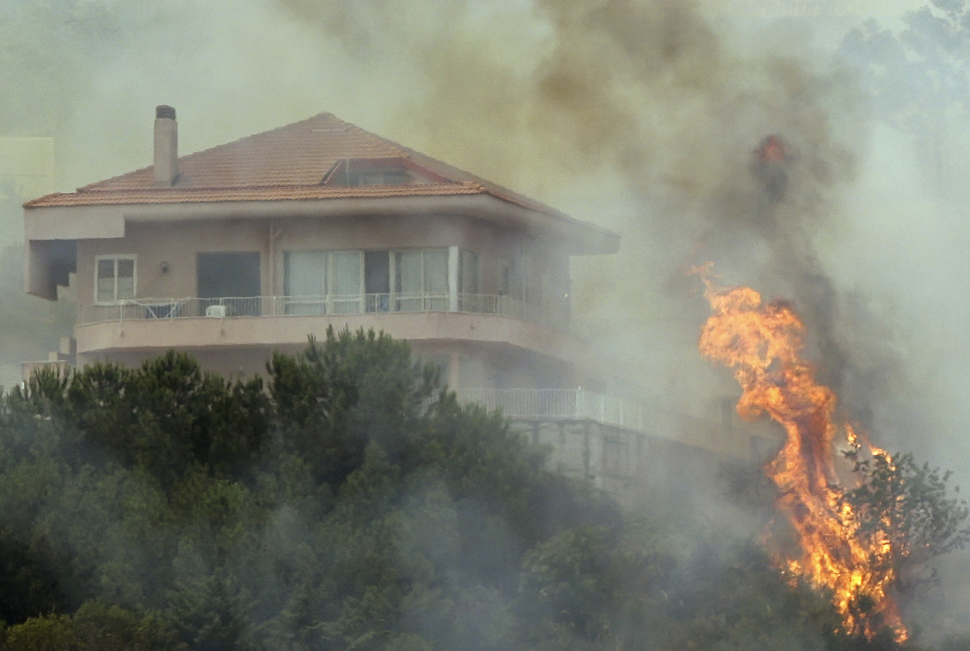Flames from a forest fire climb towards a house outside the Sicilian capital of Palermo June 26, 2007. Summer temperatures in Europe are likely to be above average this year, while northern parts will probably be wetter than normal and southern regions drier, Britain's leading forecaster said.  The house was not destroyed