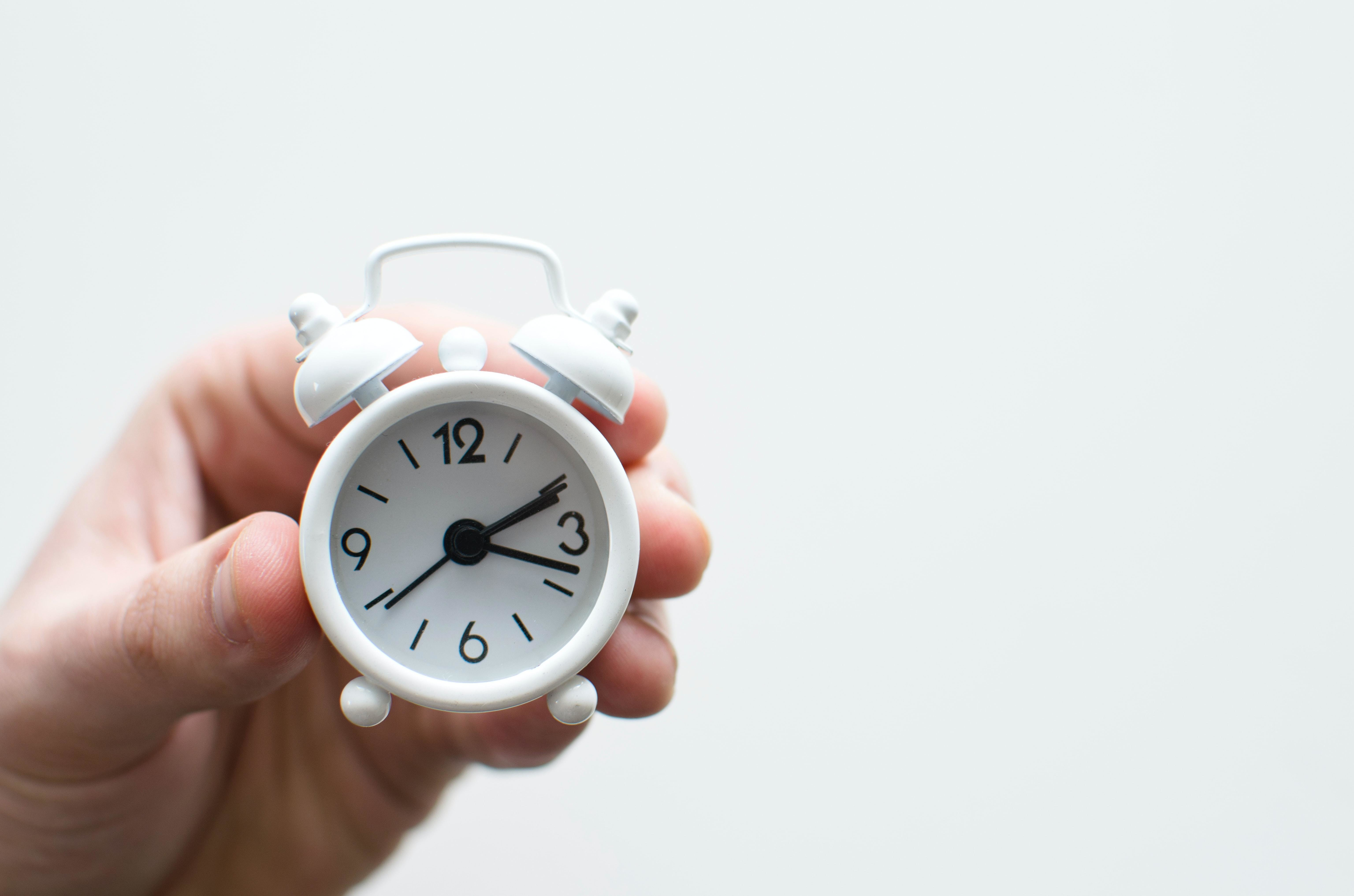 a person holding up a small alarm clock