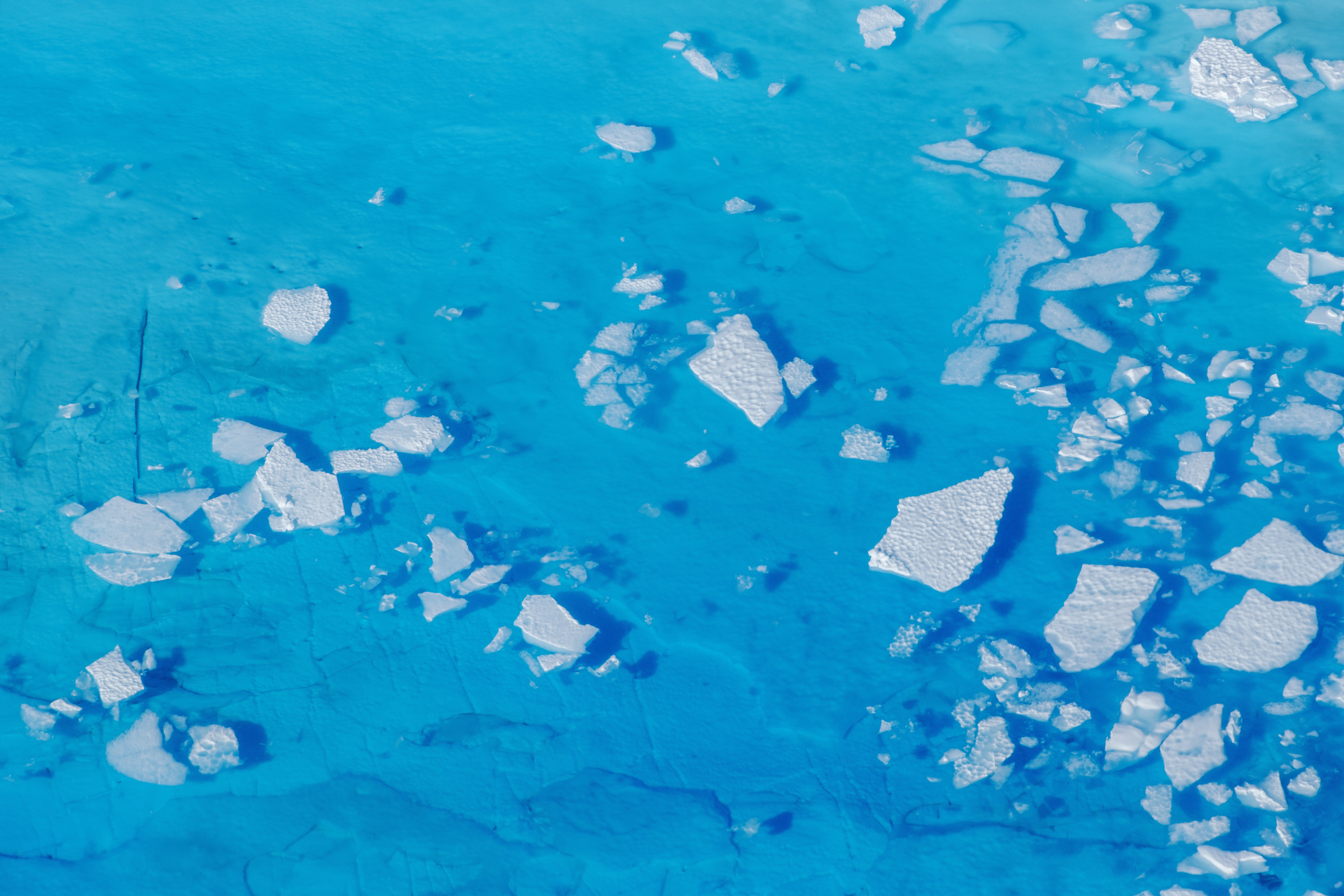 image of chunks of ice floating inside of meltwater pools on top of the Helheim glacier near Tasiilaq, Greenland