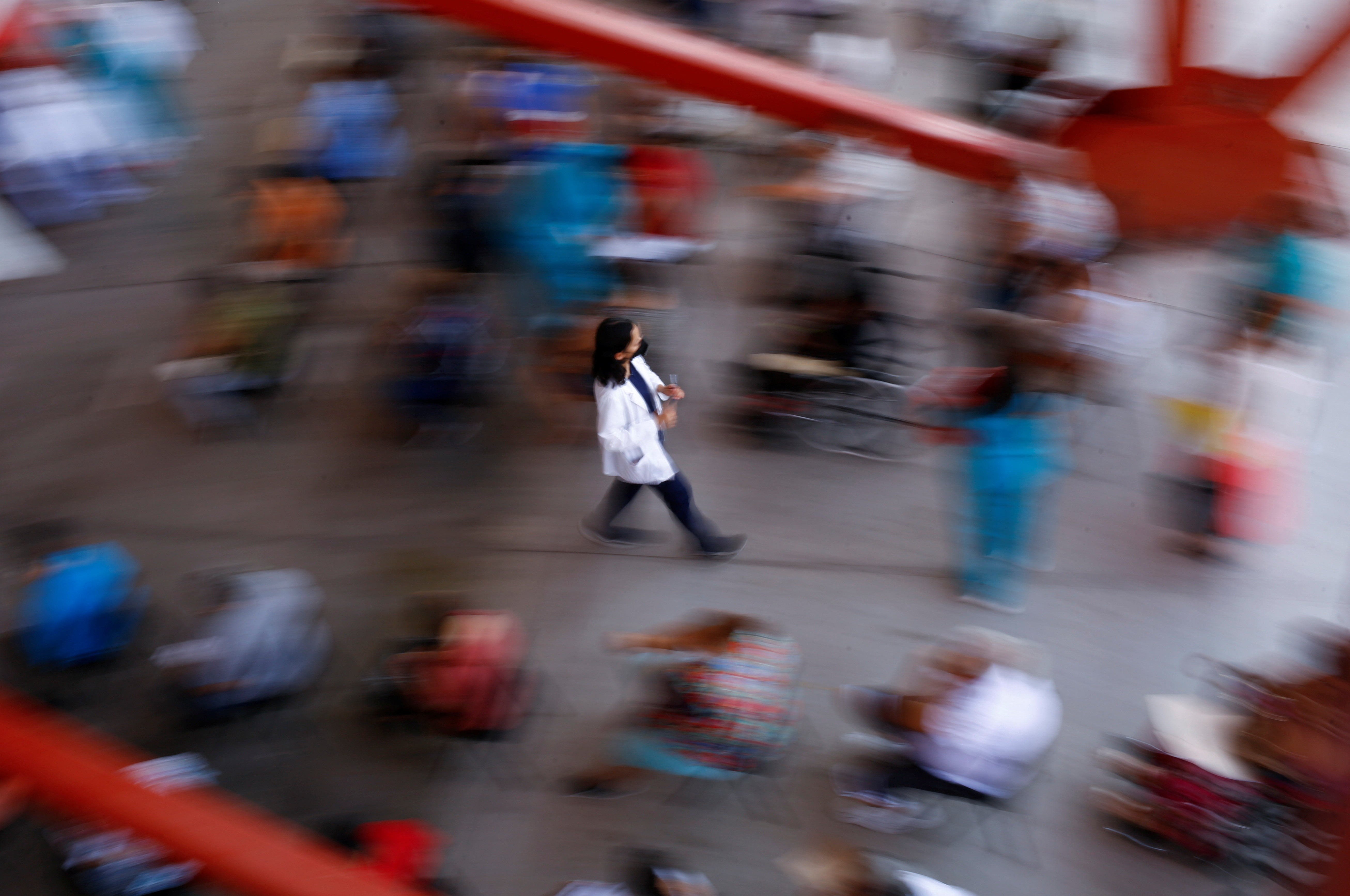 A health worker walks with a dose of the Pfizer-BioNTech coronavirus disease (COVID-19) vaccine, during a mass vaccination programme for people over 50 years of age at a baseball stadium in Ciudad Juarez, Mexico June 22, 2021. REUTERS/Jose Luis Gonzalez - RC2S5O9ZSYSN