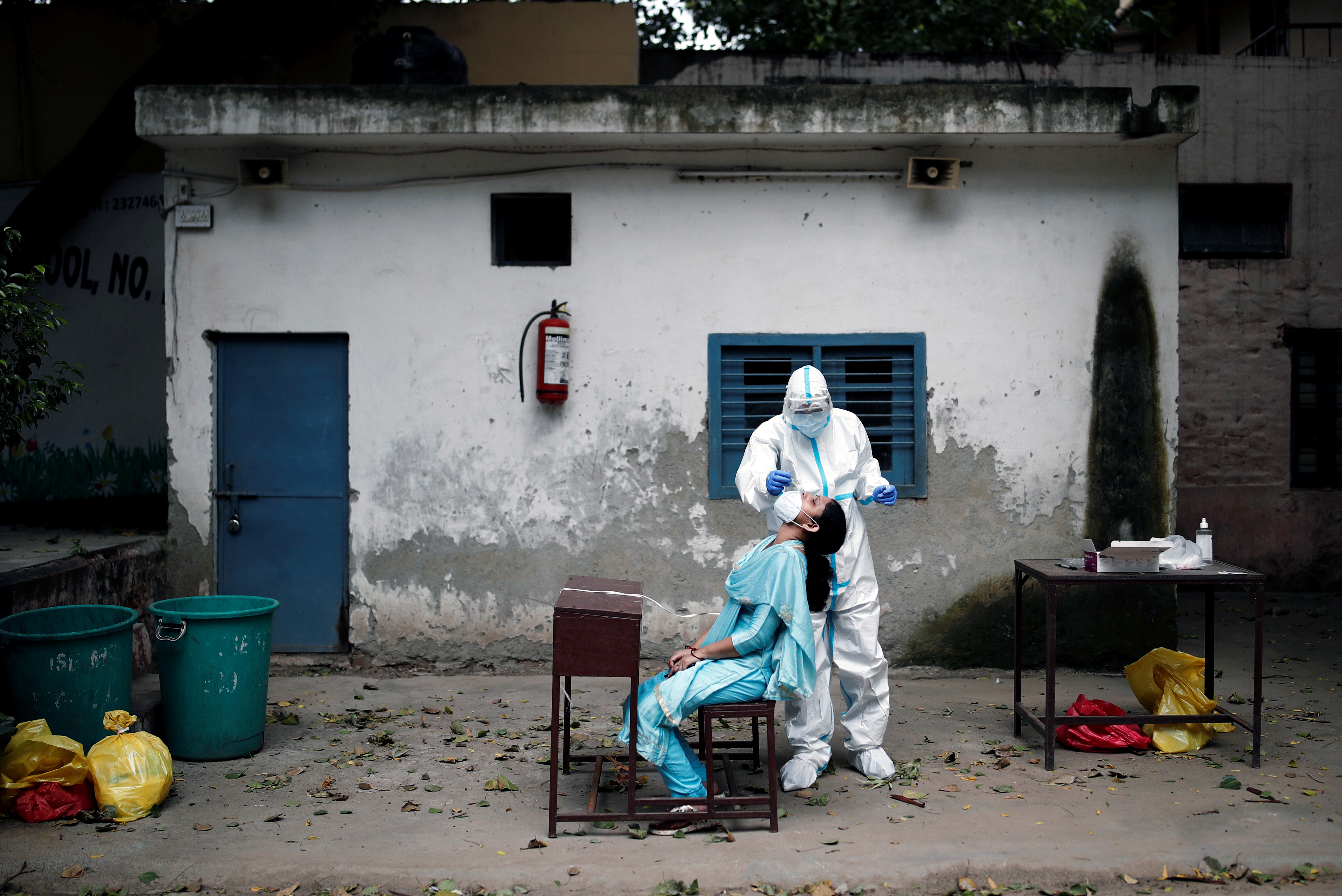 A health worker in personal protective equipment (PPE) collects a sample using a swab from a person at a school which was turned into a centre to conduct tests for the coronavirus disease (COVID-19), amidst the spread of the disease, in New Delhi, India, August 6, 2020. REUTERS/Adnan Abidi - RC2A8I9FMIBR