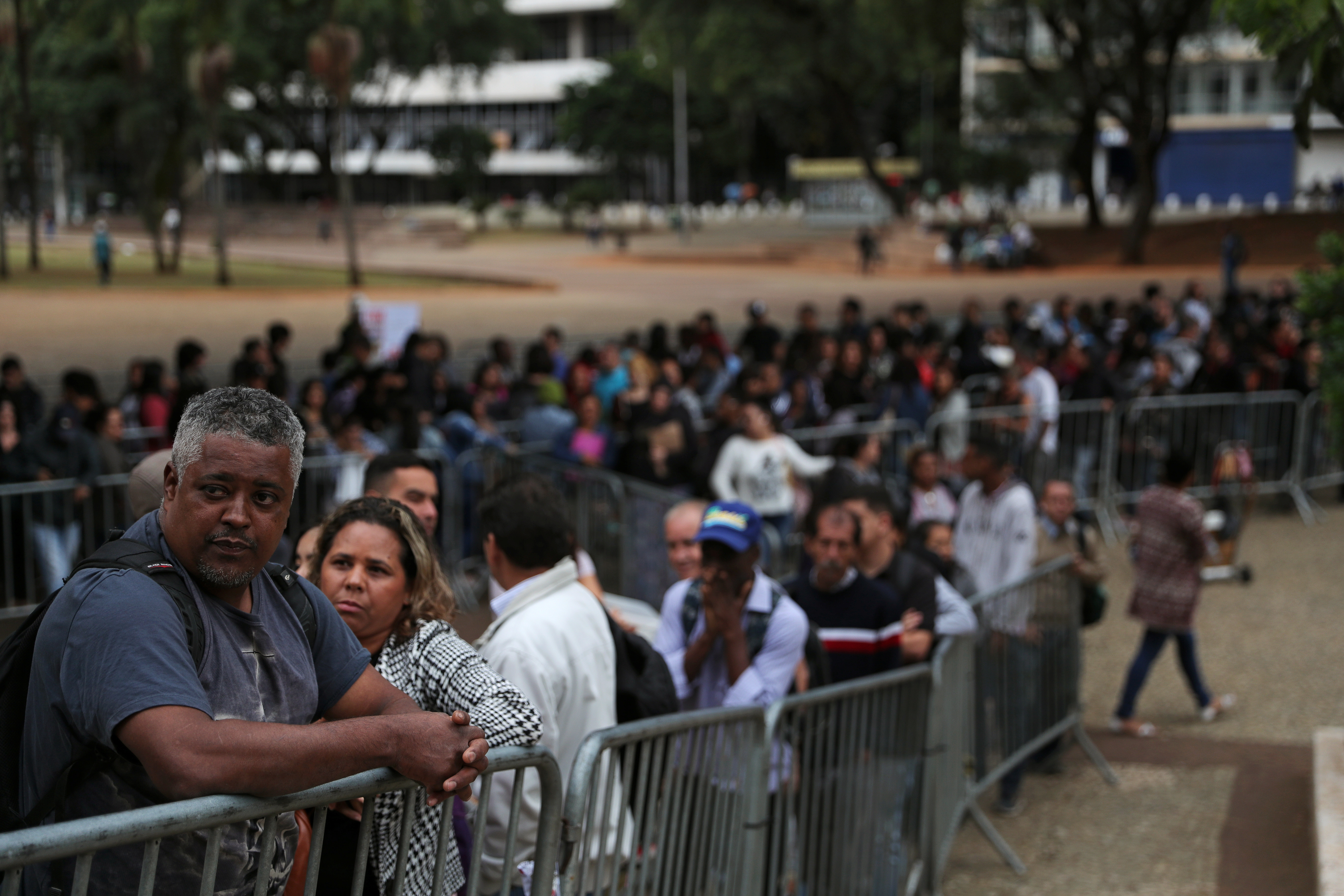 Unemployed people line up to fill out applications while looking for job opportunities in downtown Sao Paulo, Brazil.