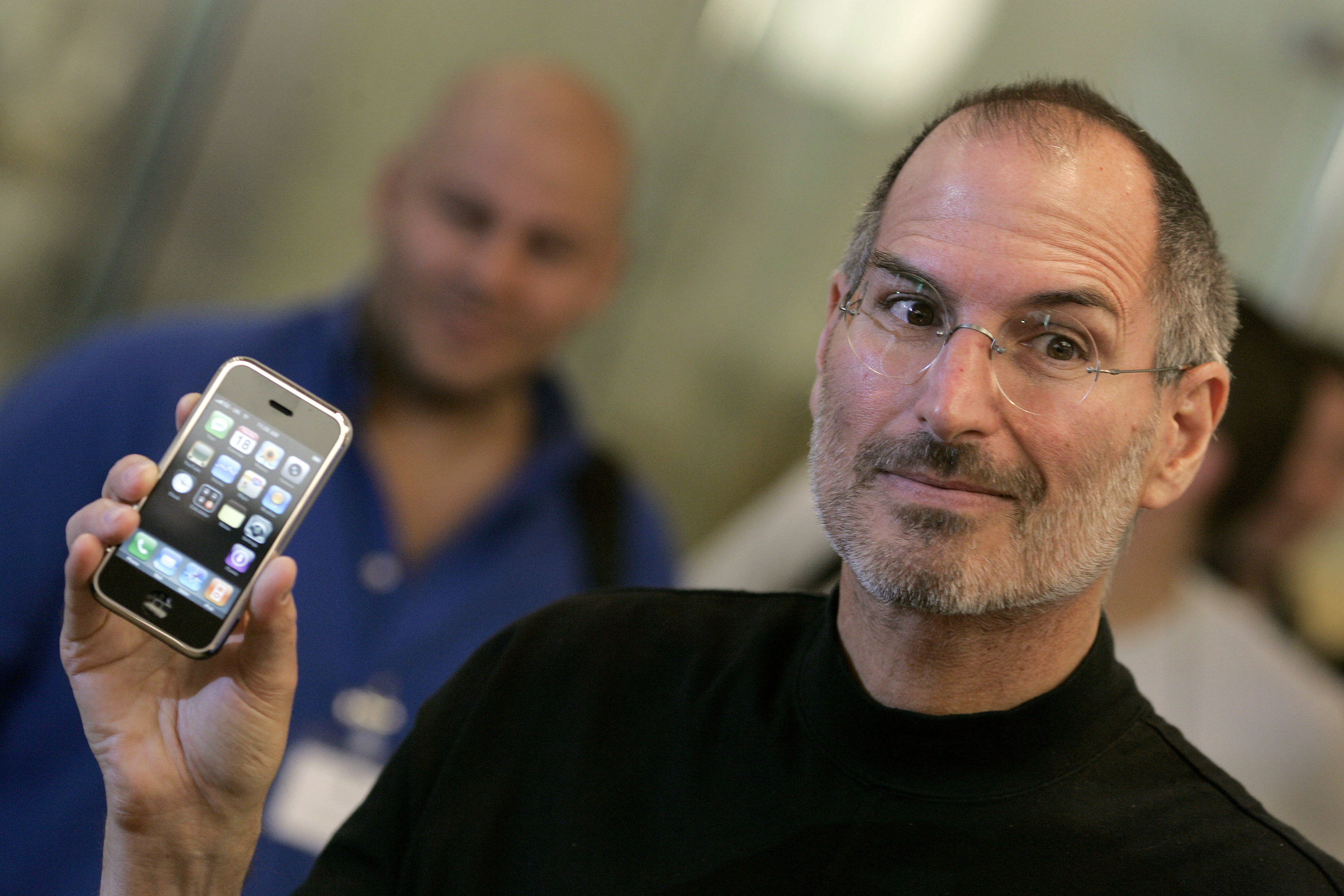 Apple Chief Executive Steve Jobs holds the new iPhone at the Apple store in central London.