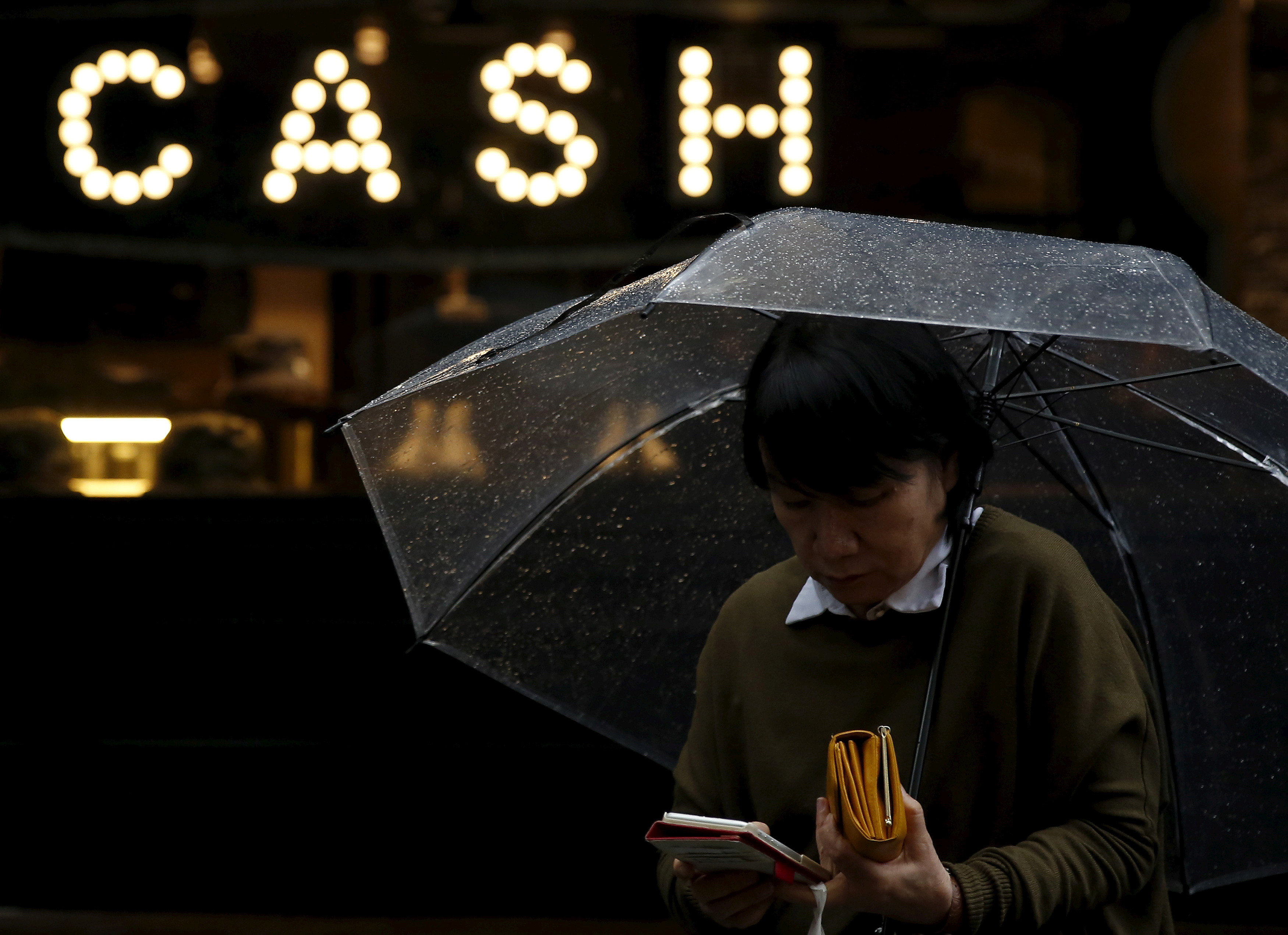 "A pedestrian holding an umbrella and her wallet walks past the word ""CASH"", part of a sign on a street at a shopping district in Tokyo, Japan, March 7, 2016.  REUTERS/Yuya Shino/File Photo                                   GLOBAL BUSINESS WEEK AHEAD PACKAGE Ð SEARCH ÒBUSINESS WEEK AHEAD 3 OCTÓ FOR ALL IMAGES - S1BEUETMAOAA"