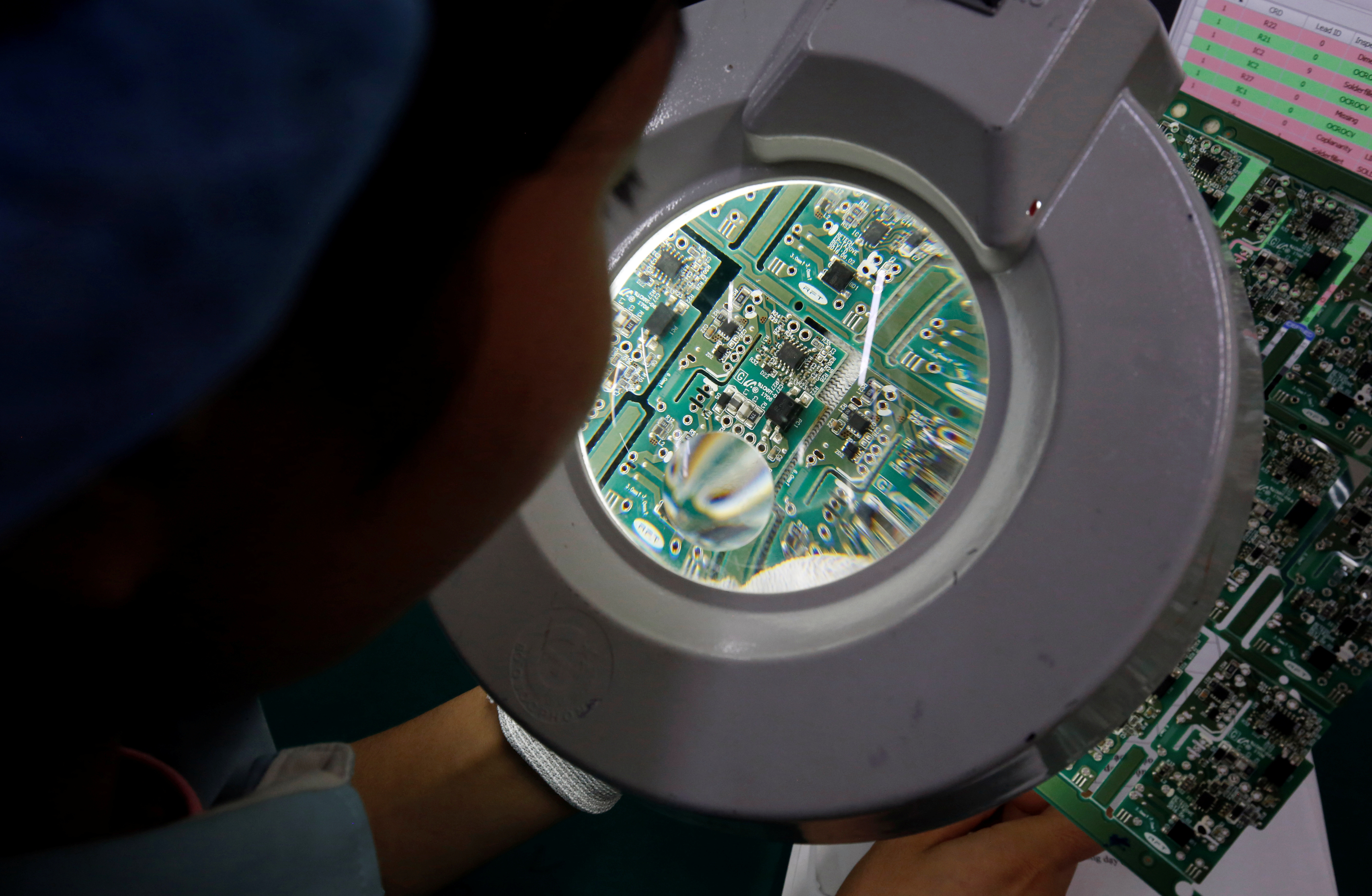A woman looks through a magnifying glass to check errors of a printer circuit board at Manutronics Factory in Bac Ninh province, Vietnam May 30, 2018. REUTERS/Kham - RC1A001B9710