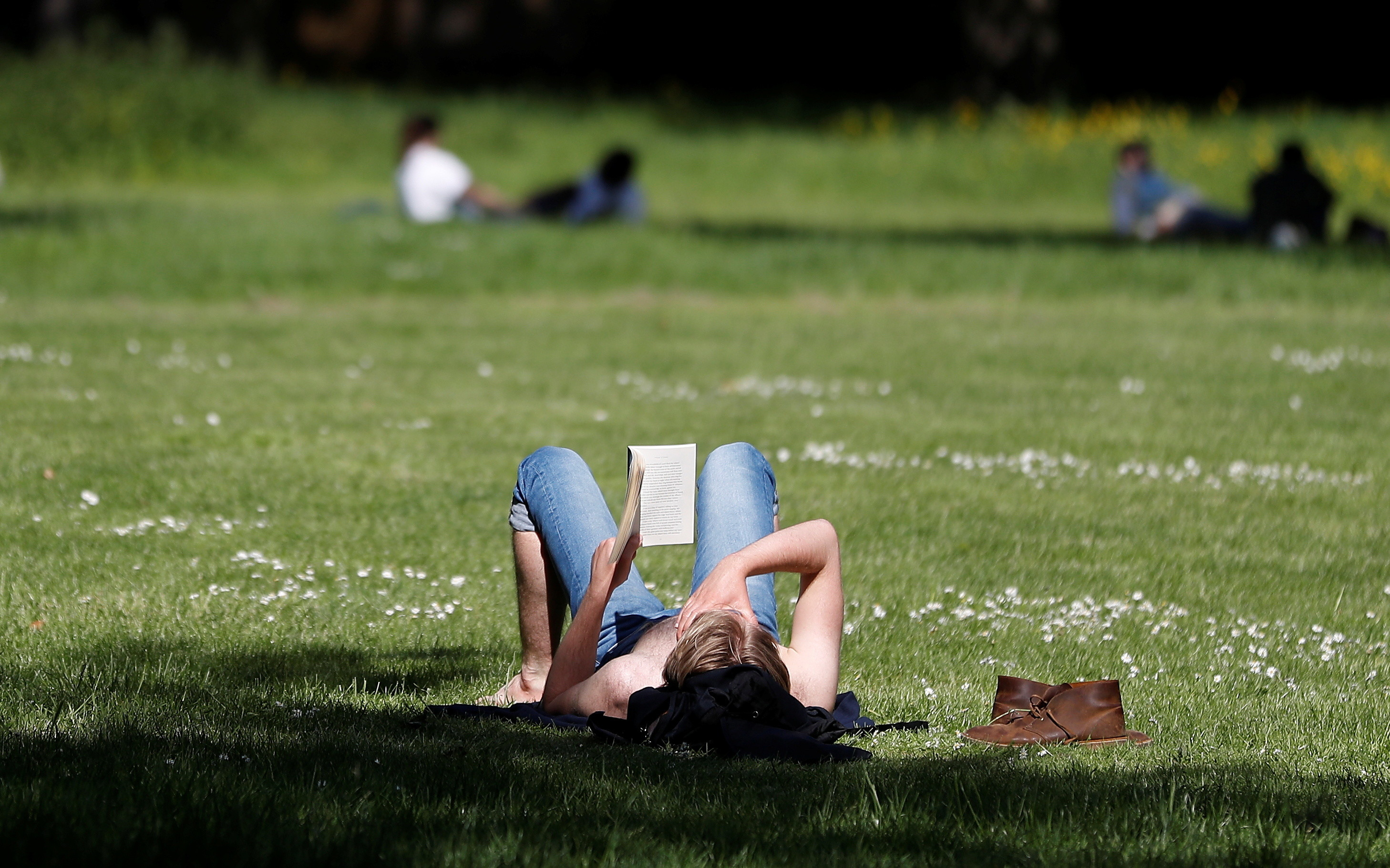 A women reads in the sunshine in Hyde Park in London, as a study finds green space can reduce loneliness.