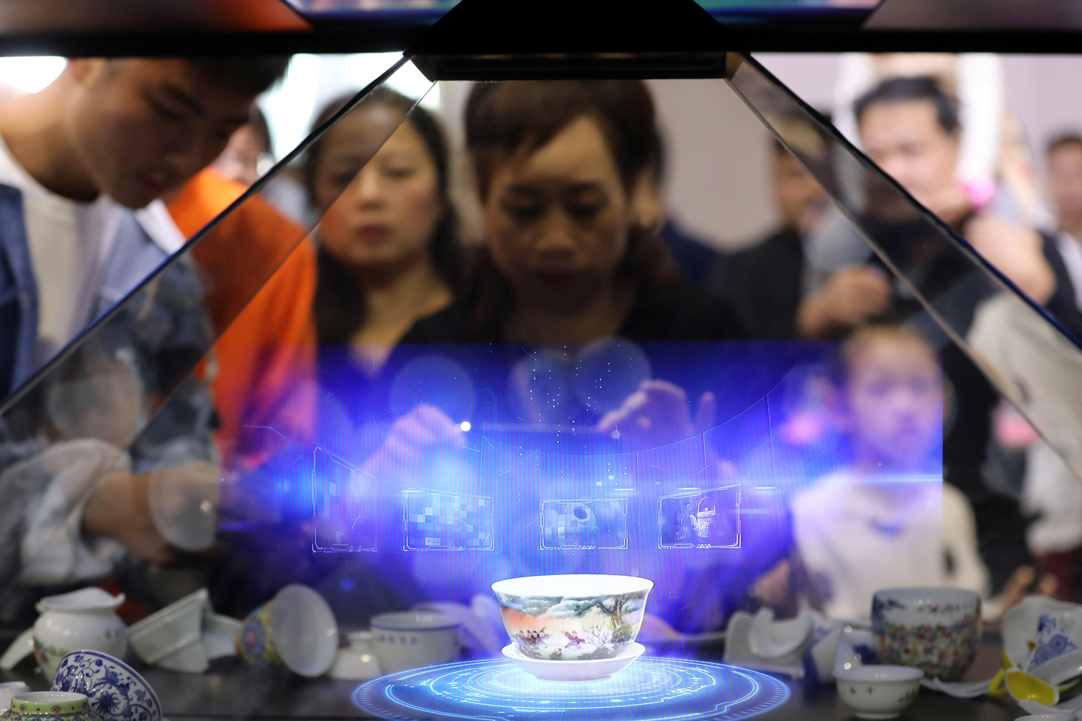 Visitors hold their phones in front of a hologram showing a porcelain teacup that is projected inside a glass cabinet during the World Conference on VR Industry in Nanchang, Jiangxi province, China October 20, 2019. Picture taken October 20, 2019. REUTERS/Stringer