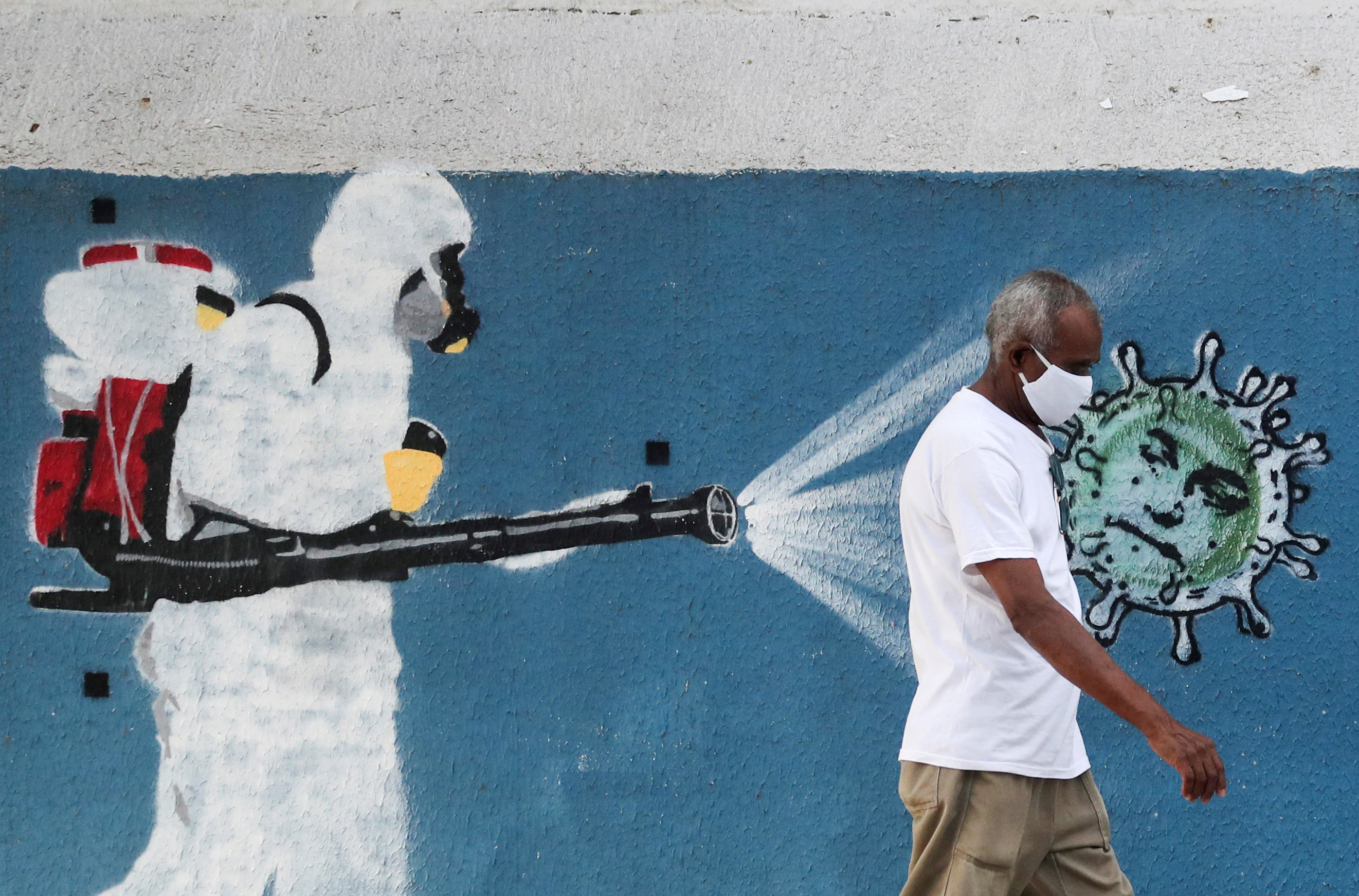 A man walks next to a graffiti depciting a cleaner wearing protective gear spraying viruses with the face of Brazil's President Jair Bolsonaro amid the coronavirus disease (COVID-19) outbreak, in Rio de Janeiro, Brazil, June 12, 2020. REUTERS/Sergio Moraes     TPX IMAGES OF THE DAY - RC2S7H971KWK