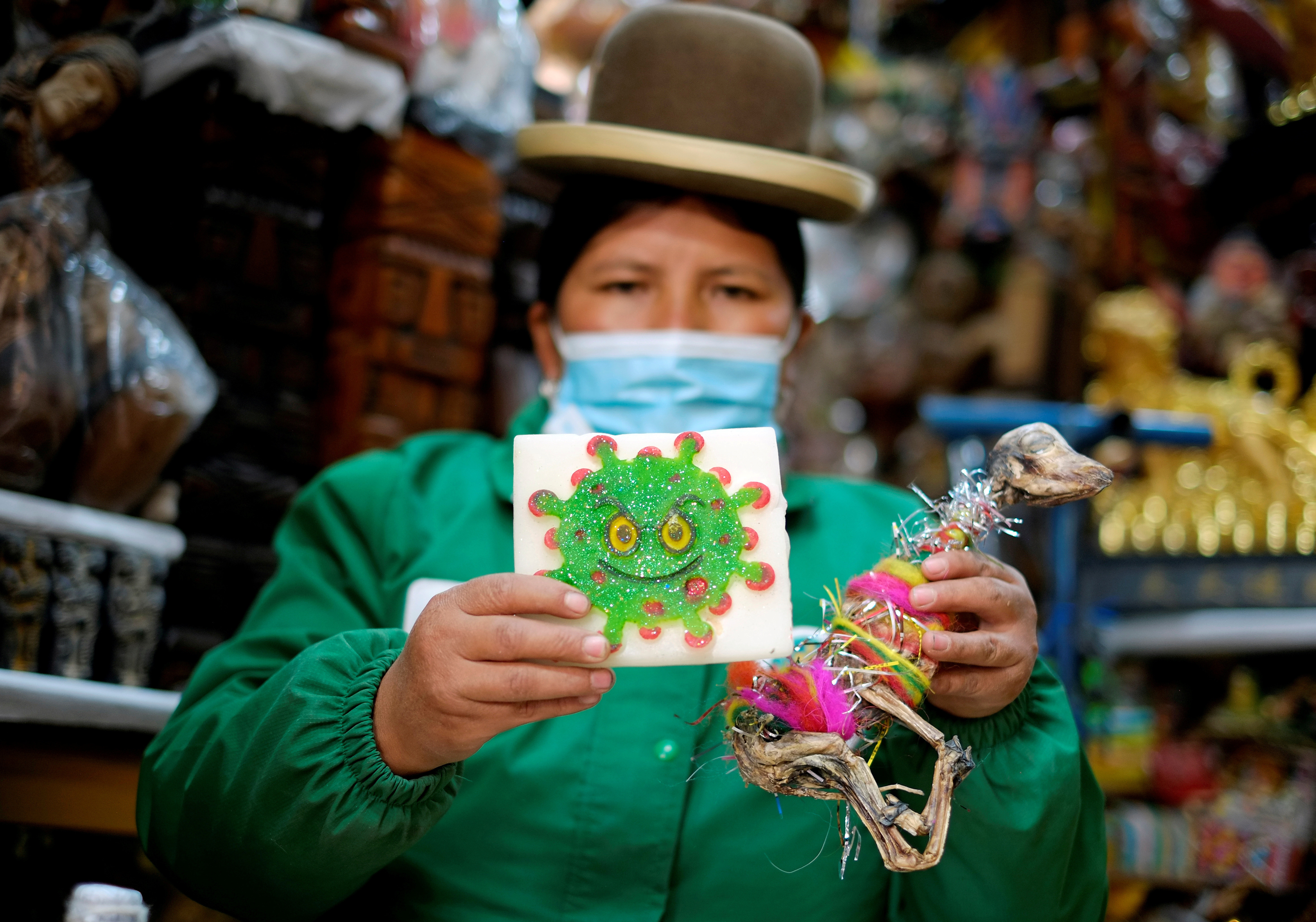 Victoria Acarapi holds a figure of the coronavirus and a llama fetus as part of an offering during the Pachamama (Mother Earth) month at the witches market, amid the outbreak of the coronavirus disease (COVID-19) in La Paz, Bolivia August 1, 2020. Picture taken August 1, 2020. REUTERS/David Mercado     TPX IMAGES OF THE DAY - RC2J6I9G3XZ6