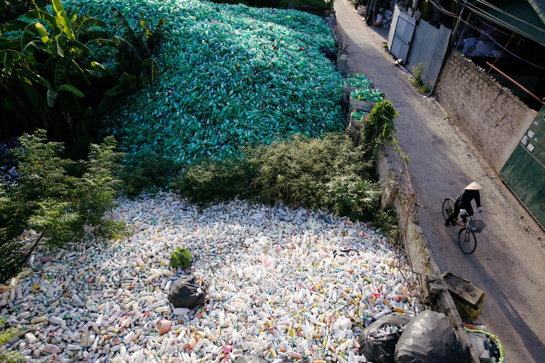 A Vietnamese woman rides past recyclable plastic bottles.