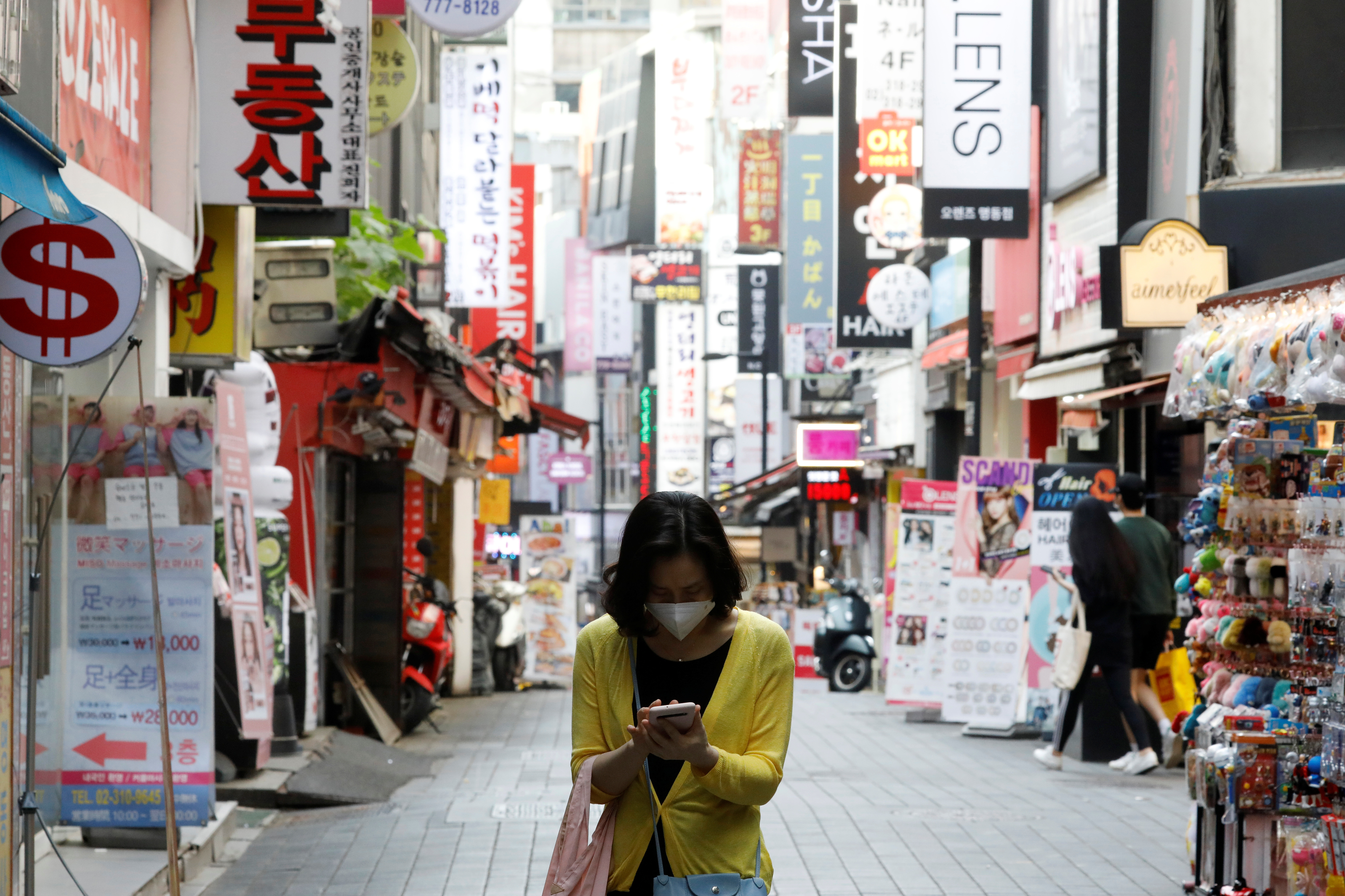 A woman wearing a mask looks at her mobile phone amid social distancing measures to avoid the spread of the coronavirus disease (COVID-19), in Myeongdong shopping district in Seoul, South Korea, May 28, 2020.   REUTERS/Kim Hong-Ji - RC2OXG90N3B6