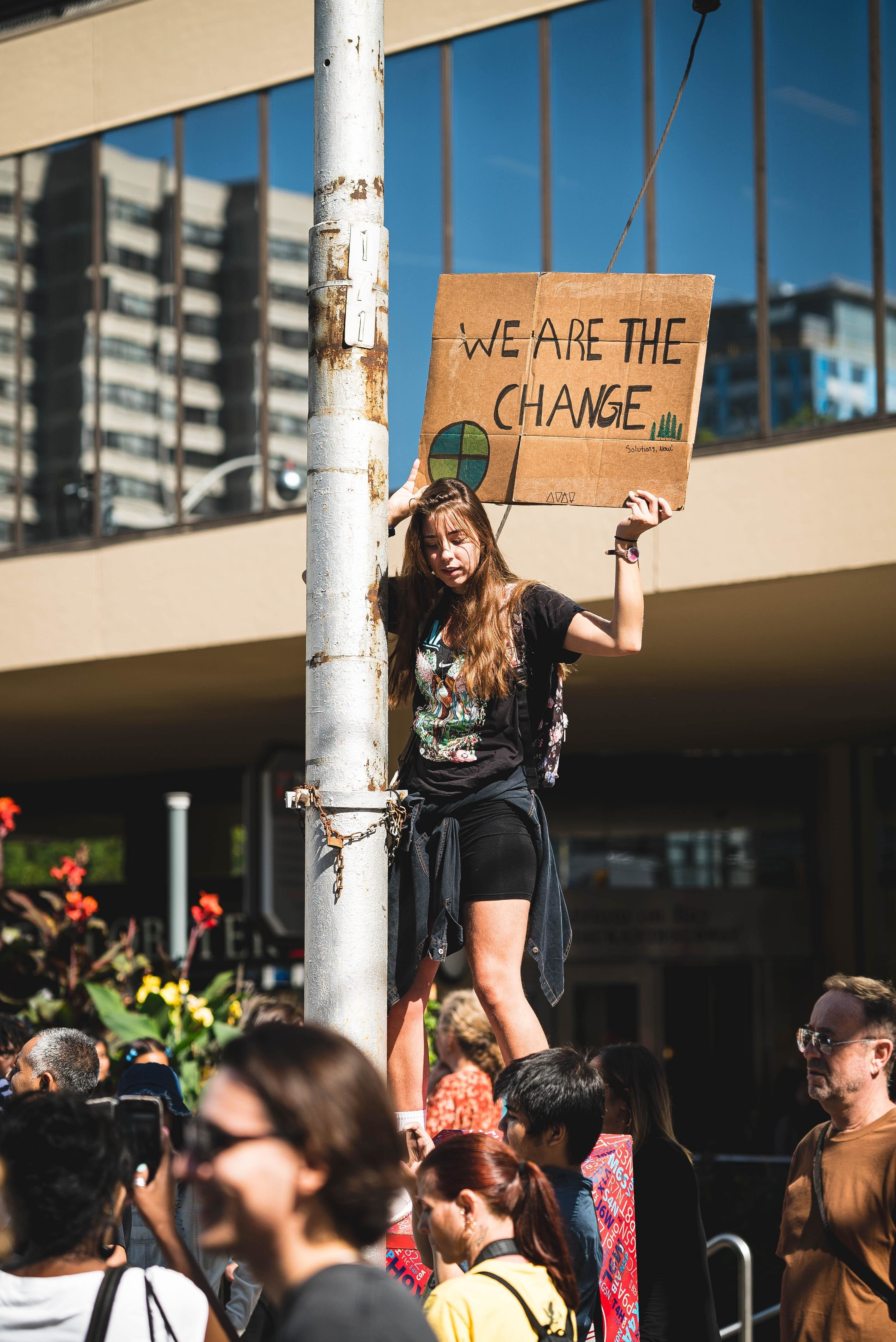Woman in black top holding climate protest placard