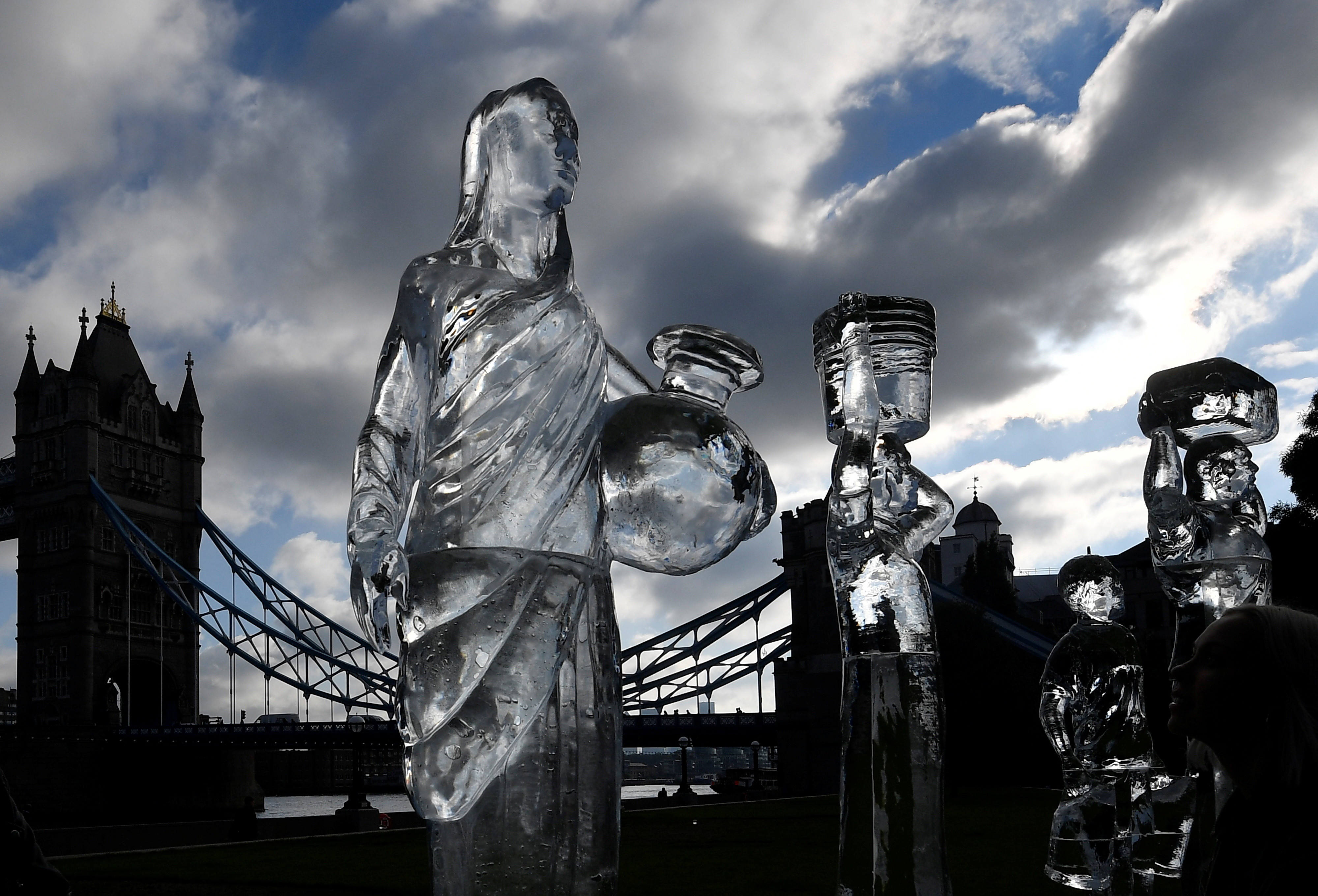 Ice sculptures depicting people walking to collect clean water are seen as environmental and public health campaign group WaterAid highlights the threat posed globally by climate change to healthy water supplies, near Tower Bridge, in London, Britain, September 15, 2021. REUTERS/Toby Melville - RC28QP9HEO58