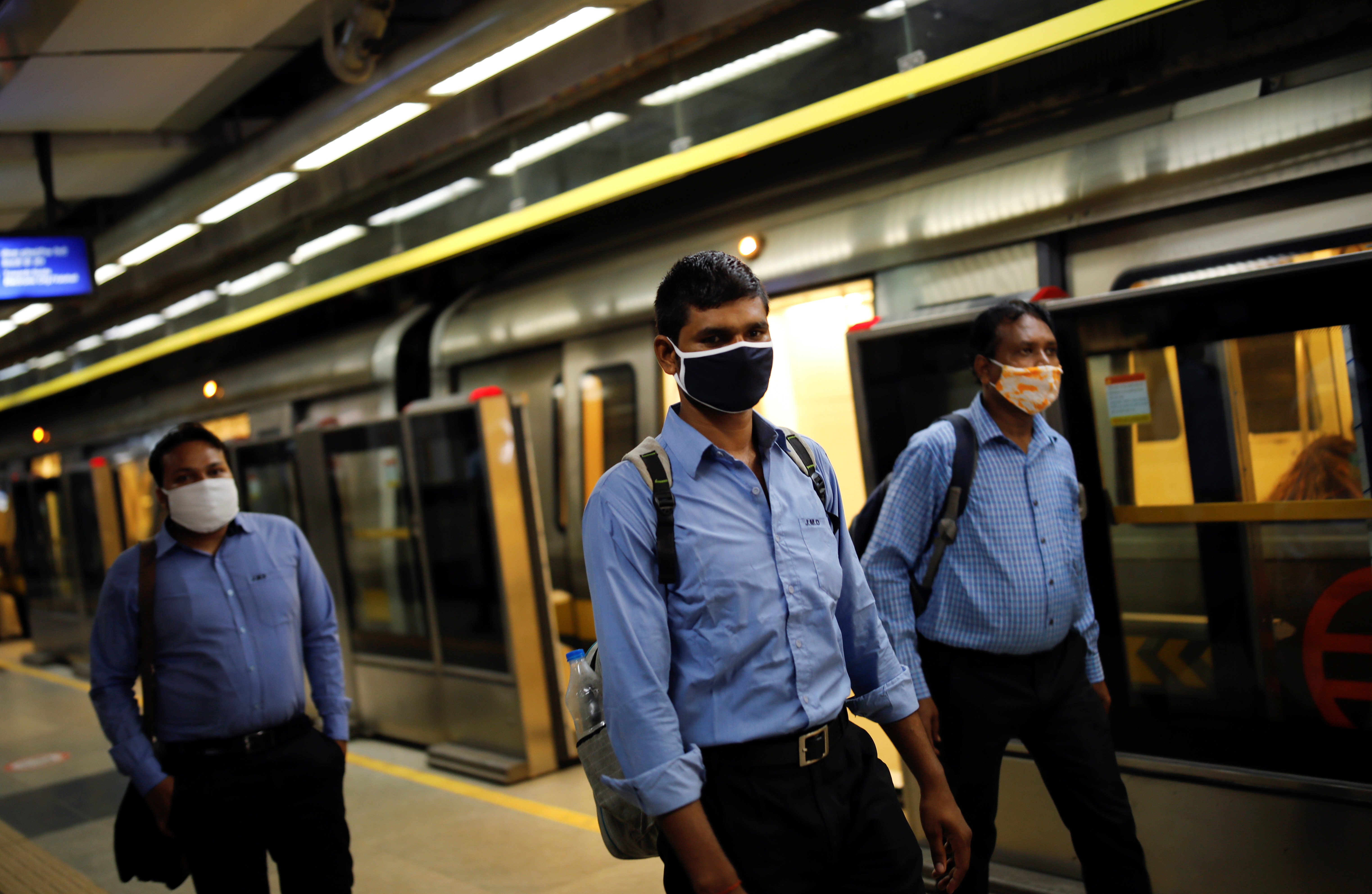 Commuters wearing face masks walk at a Delhi metro train station, on the first day of the restart of their operations, amidst the spread of coronavirus disease (COVID-19), in New Delhi, India, September 7, 2020. REUTERS/Adnan Abidi - RC2ITI9J5OUB