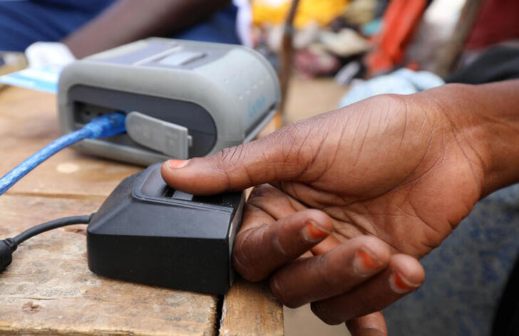 Isha Hassan Abdinur uses biometric fingerprint to sign for her online shopping from the World Food Program (WFP) in Daynile district of Mogadishu, Somalia October 26, 2020. Picture taken October 26, 2020.