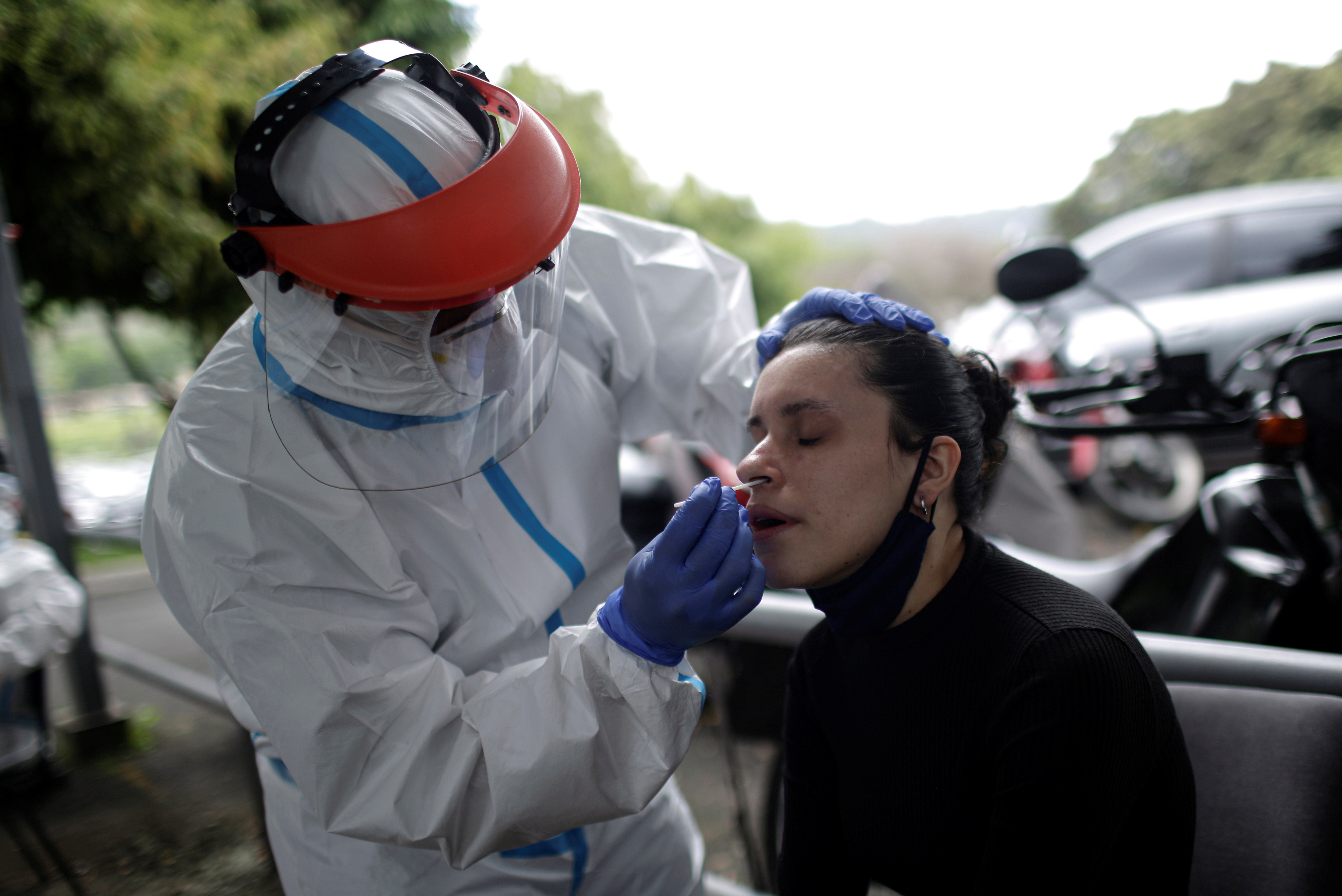 A healthcare worker takes a swab from a woman for the coronavirus disease (COVID-19) test, in a slum area in San Jose, Costa Rica July 7, 2020. REUTERS/Juan Carlos Ulate - RC2LOH9A3B74