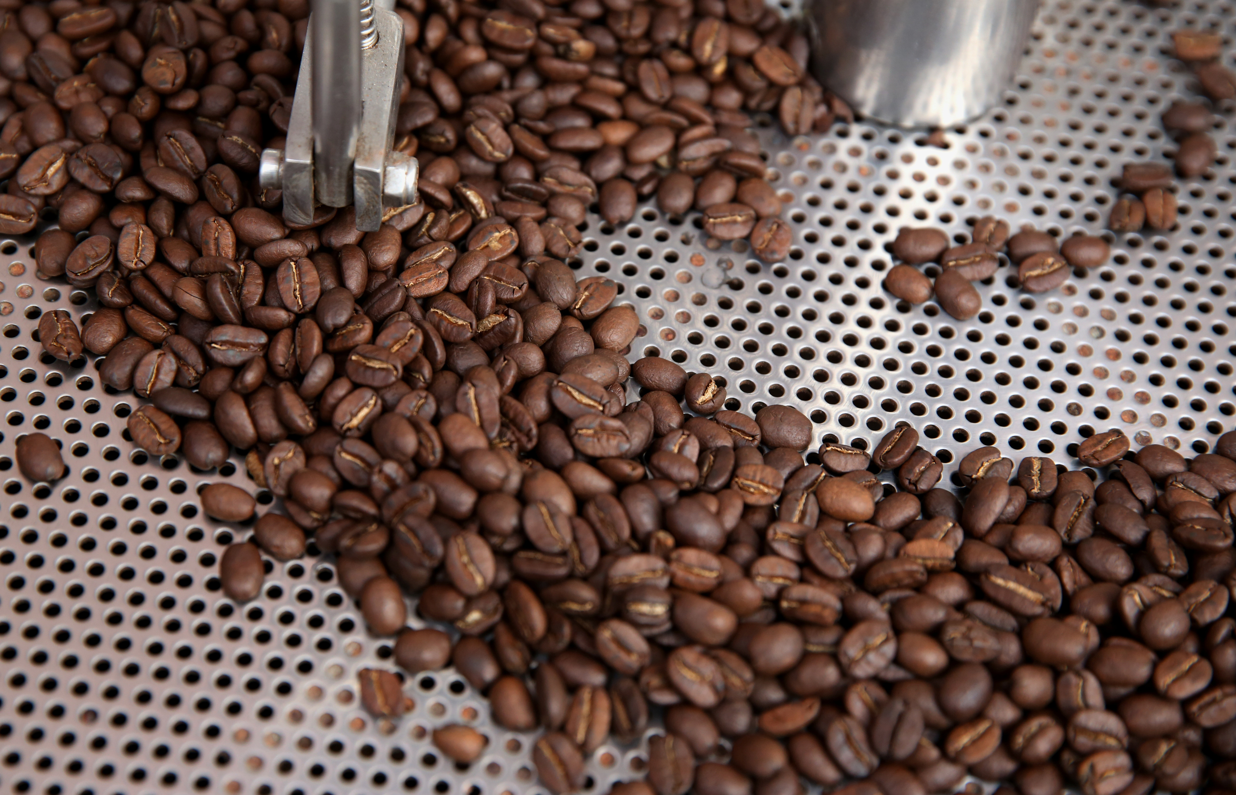 Coffee beans are seen in a roaster at a stand at the Coffee Fair in Lima, Peru, August 25, 2017.