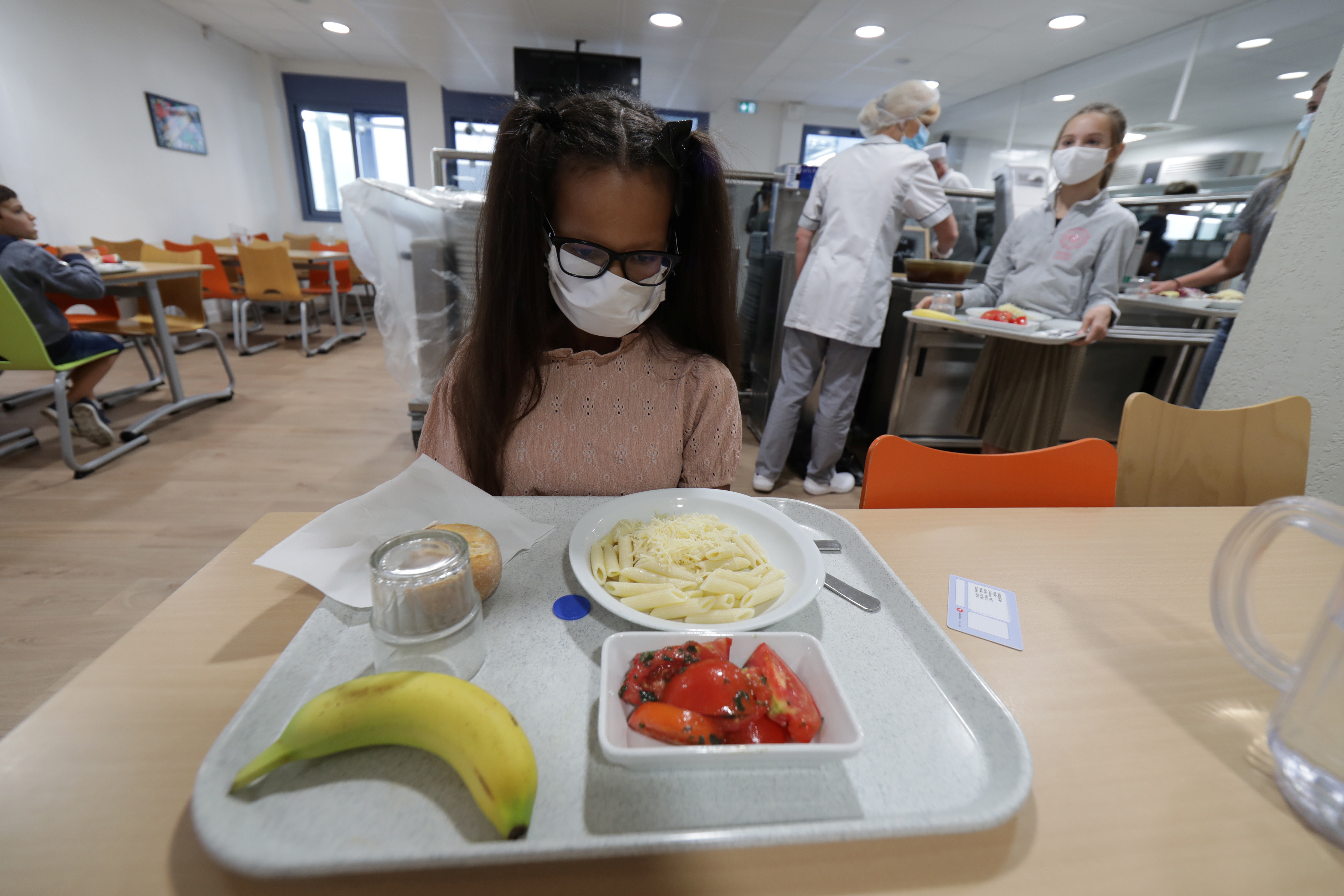A secondary school student, wearing a protective face mask, sits in front of her meal tray in the school canteen room at the College Henri Matisse school during its reopening in Nice as French children return to their schools after the summer break with protective face masks and social distancing as part of efforts to curb a resurgence of the coronavirus disease (COVID-19) across France, September 1, 2020. REUTERS/Eric Gaillard - RC2MPI920XA0